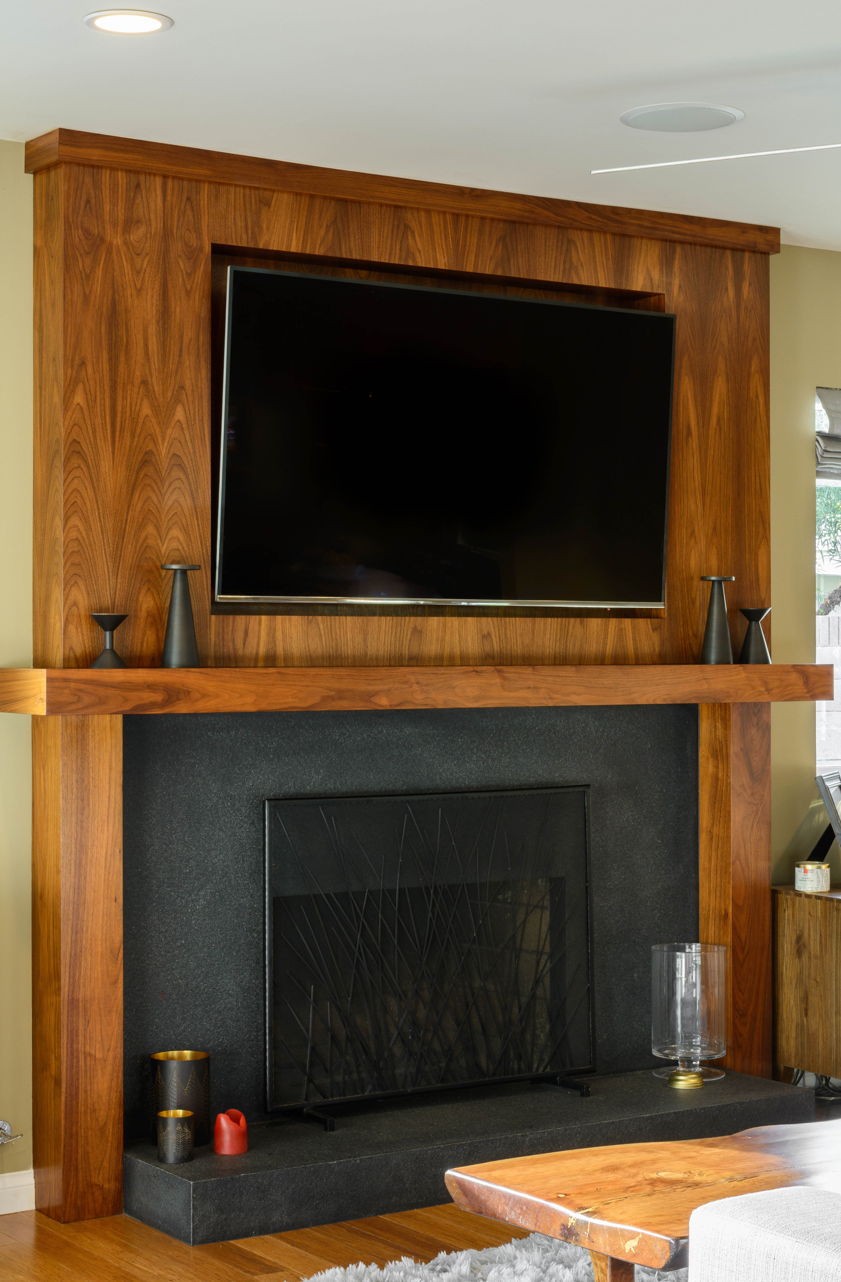 Fireplace with a stone hearth and custom-built walnut surround