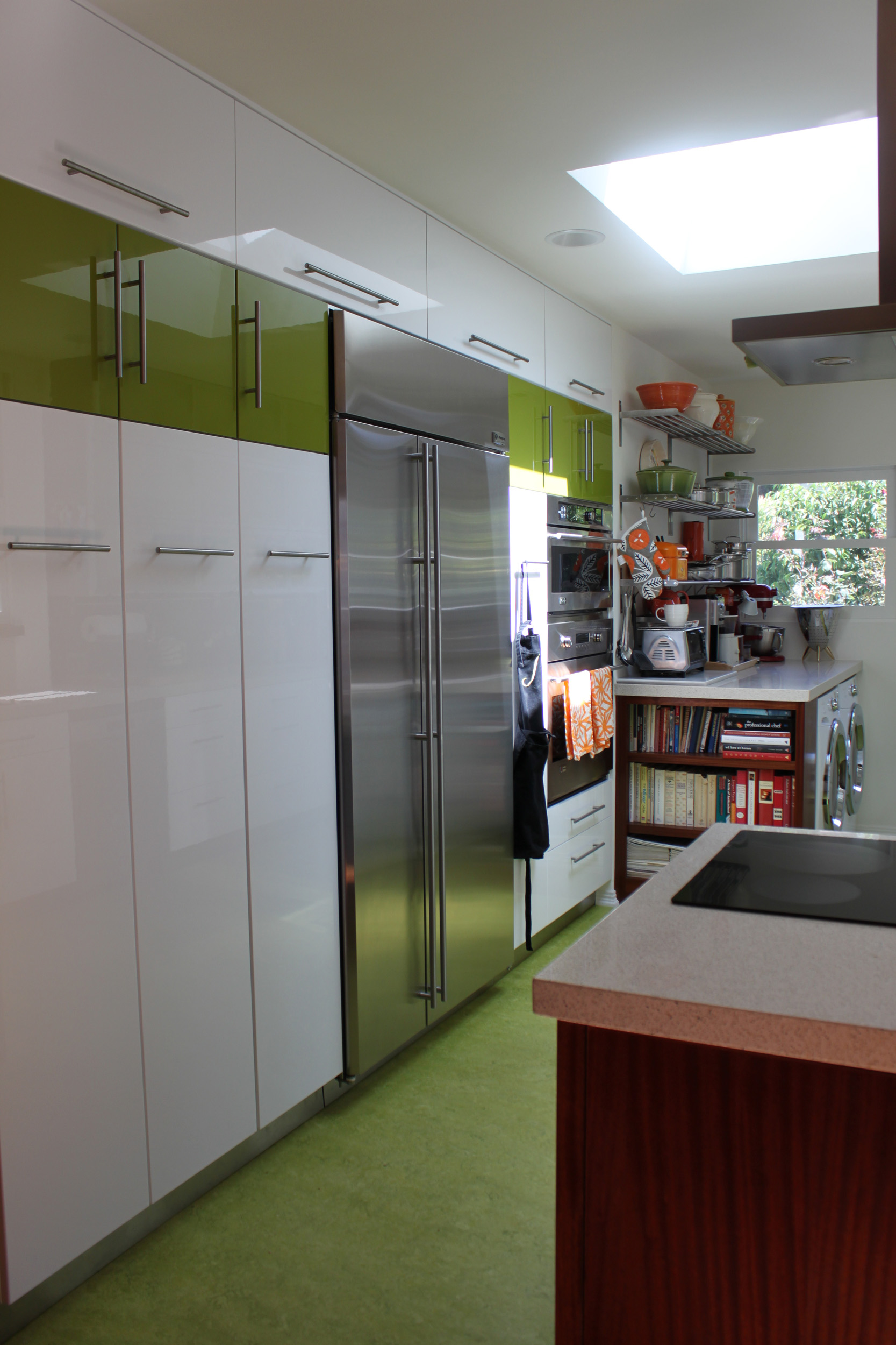 Small colorful modern kitchen with white and green cabinets, green flooring and custom-built oiled finish cabinetry