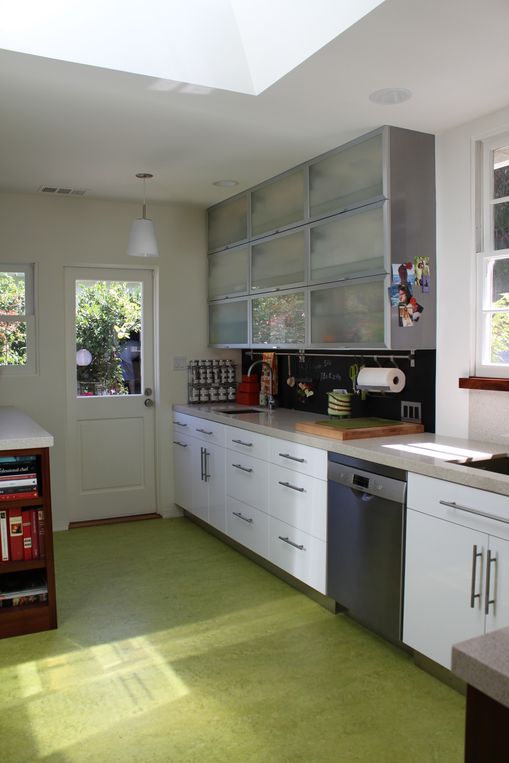 Bright and lively small modern kitchen with white cabinets, glass awning uppers, quartz countertops, blackboard backsplash, bar sink, and green flooring
