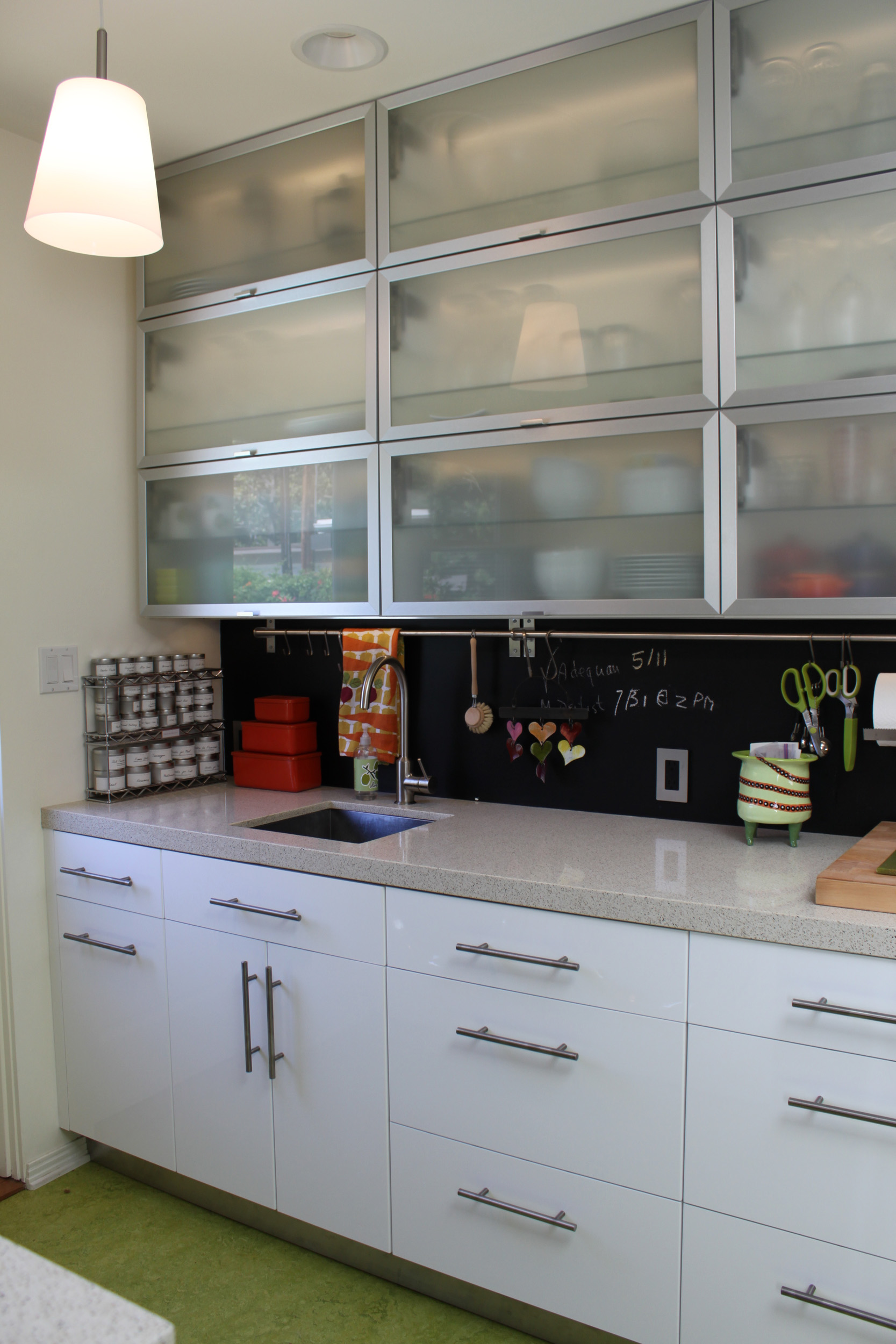 Colorful modern kitchen with white cabinets and awning uppers, blackboard backsplash and green flooring
