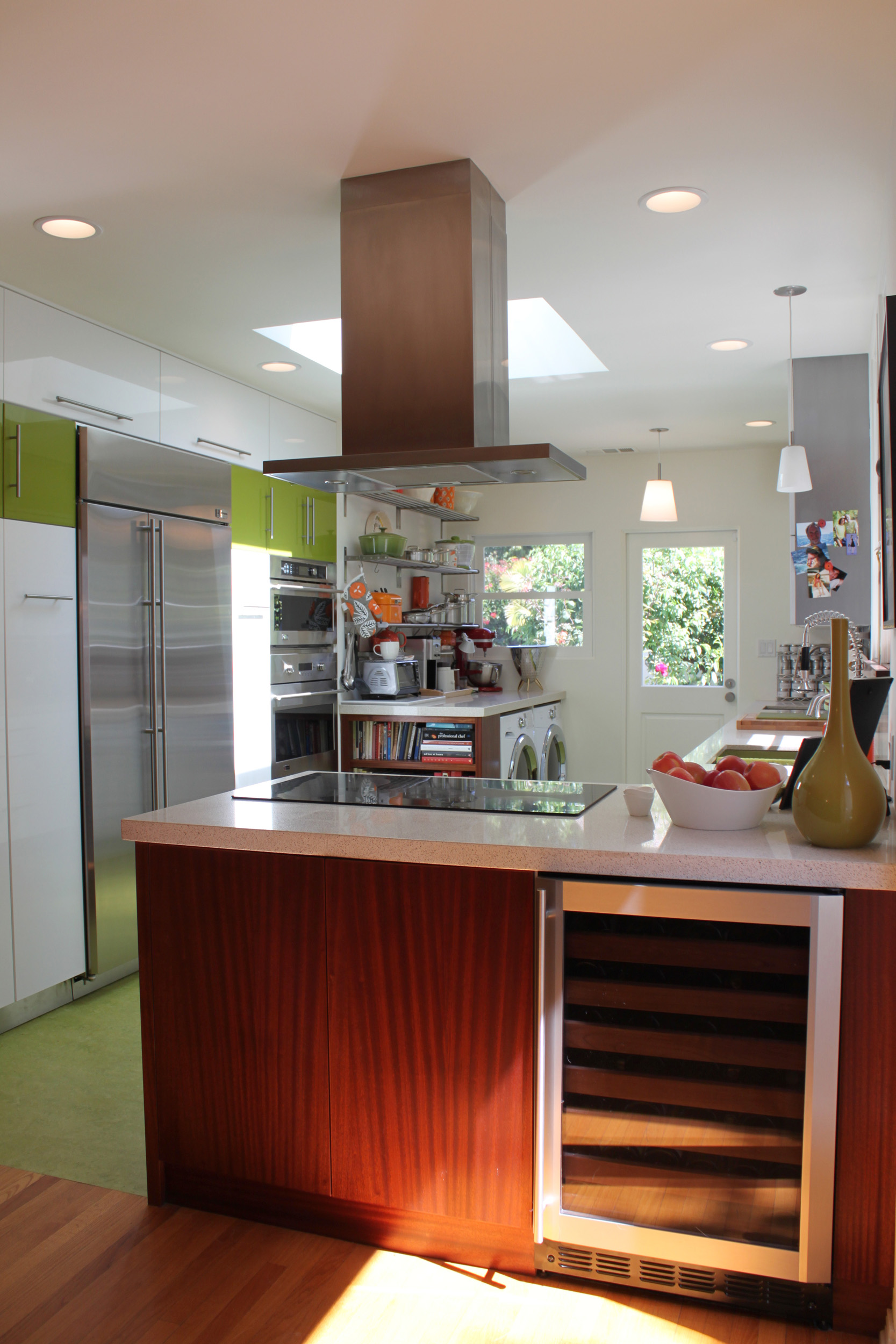 Kitchen peninsula with electric cooktop, island mount range hood and wine cooler