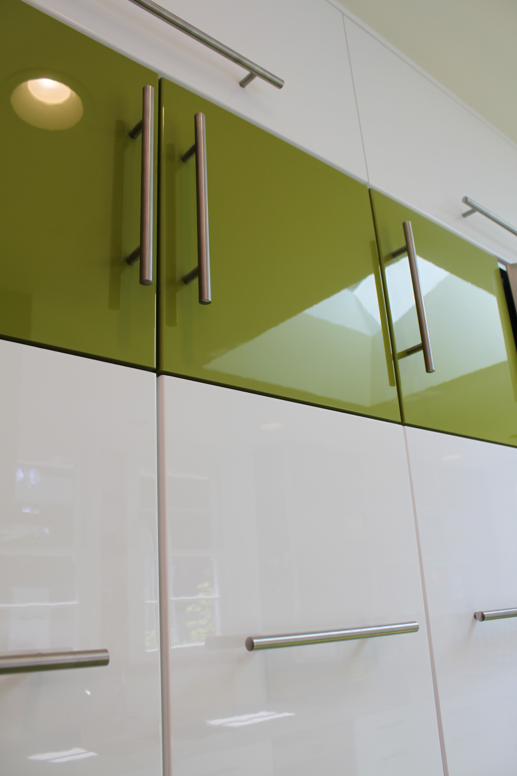 White full height kitchen cabinets with a playful and creative touch of green and a mixture of openings