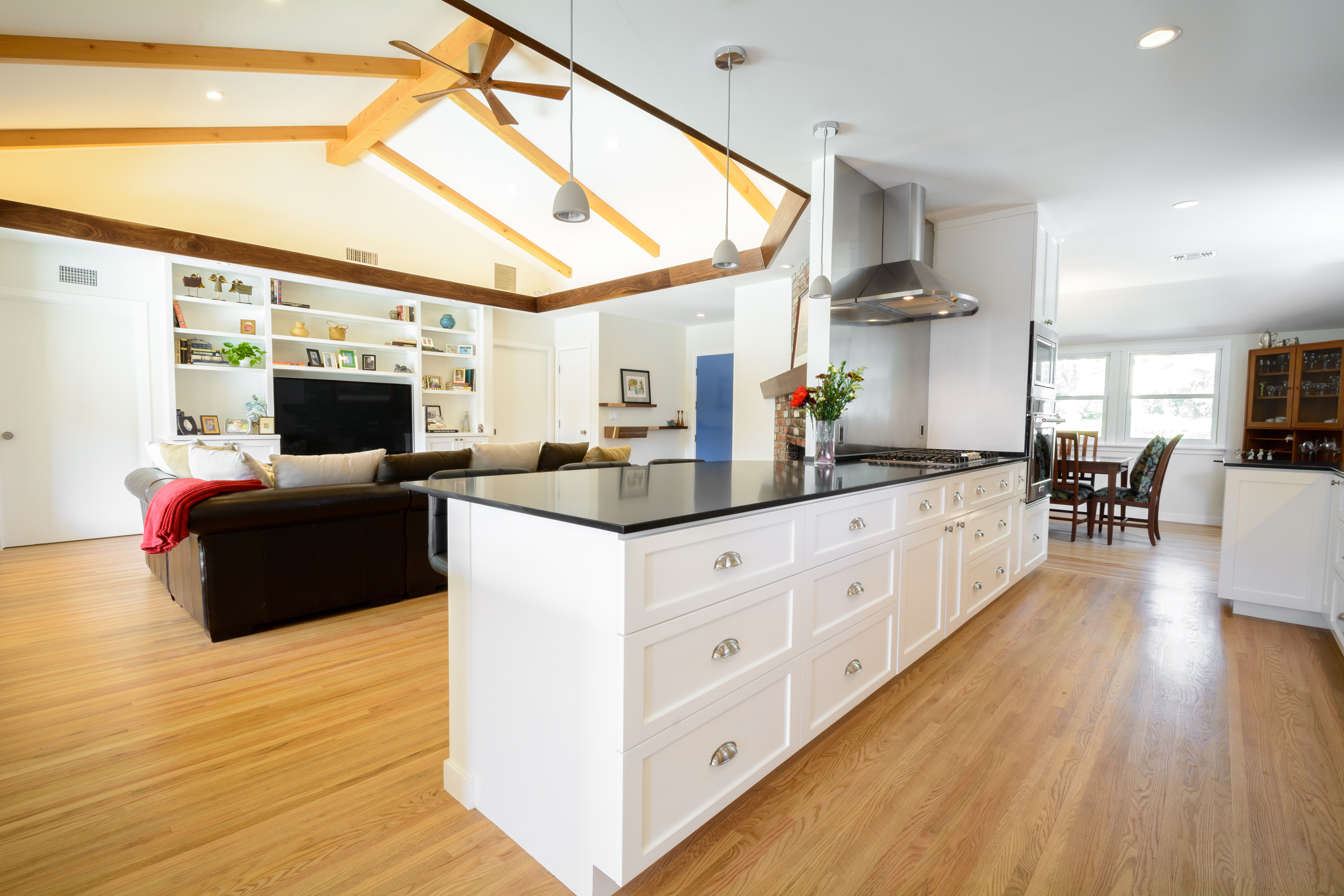 This open kitchen floor plan giving onto the living and dining rooms creates an overall bright and inviting space as well as an easy flow for this Claremont mid-century ranch residence