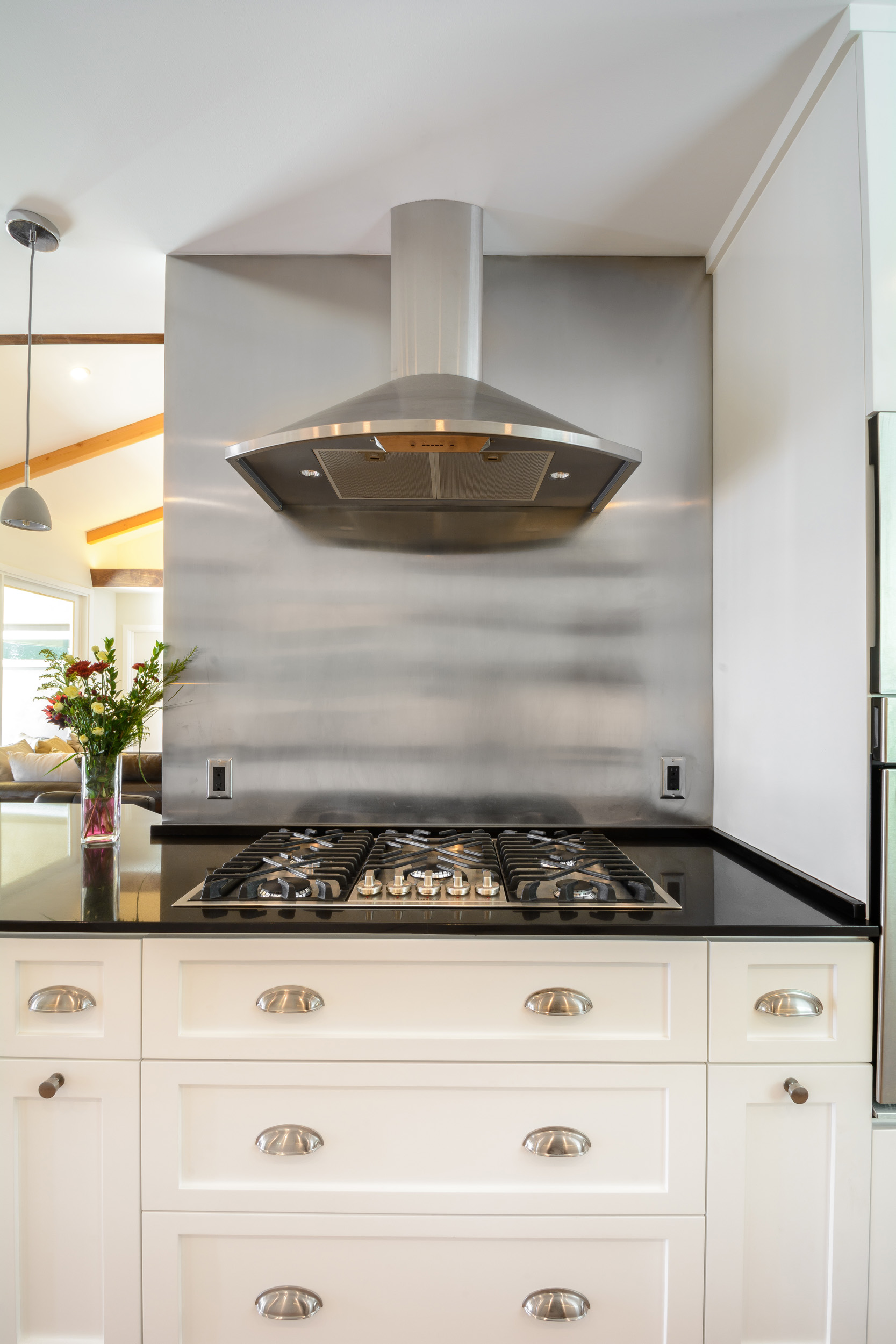 Stainless steel 5-burner cooktop and wall-mounted hood over white shaker cabinets with black quartz countertop and stainless steel backsplash