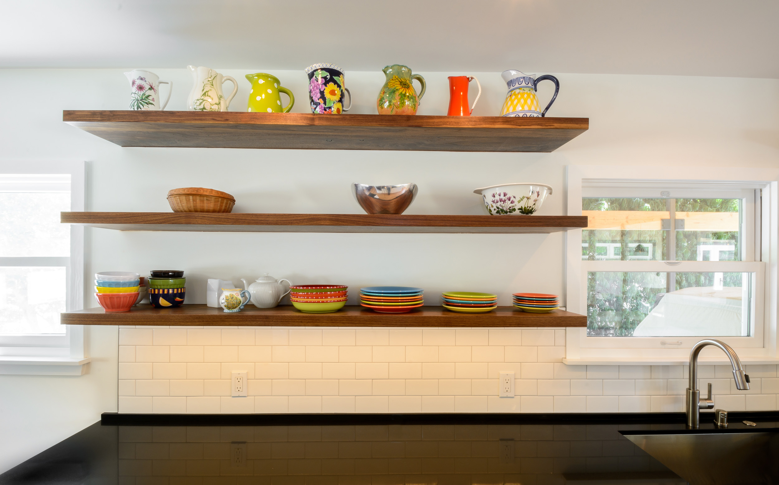 Open shelving design for this mid-century ranch kitchen: walnut floating shelves over a black quartz countertop and a white subway tile backsplash