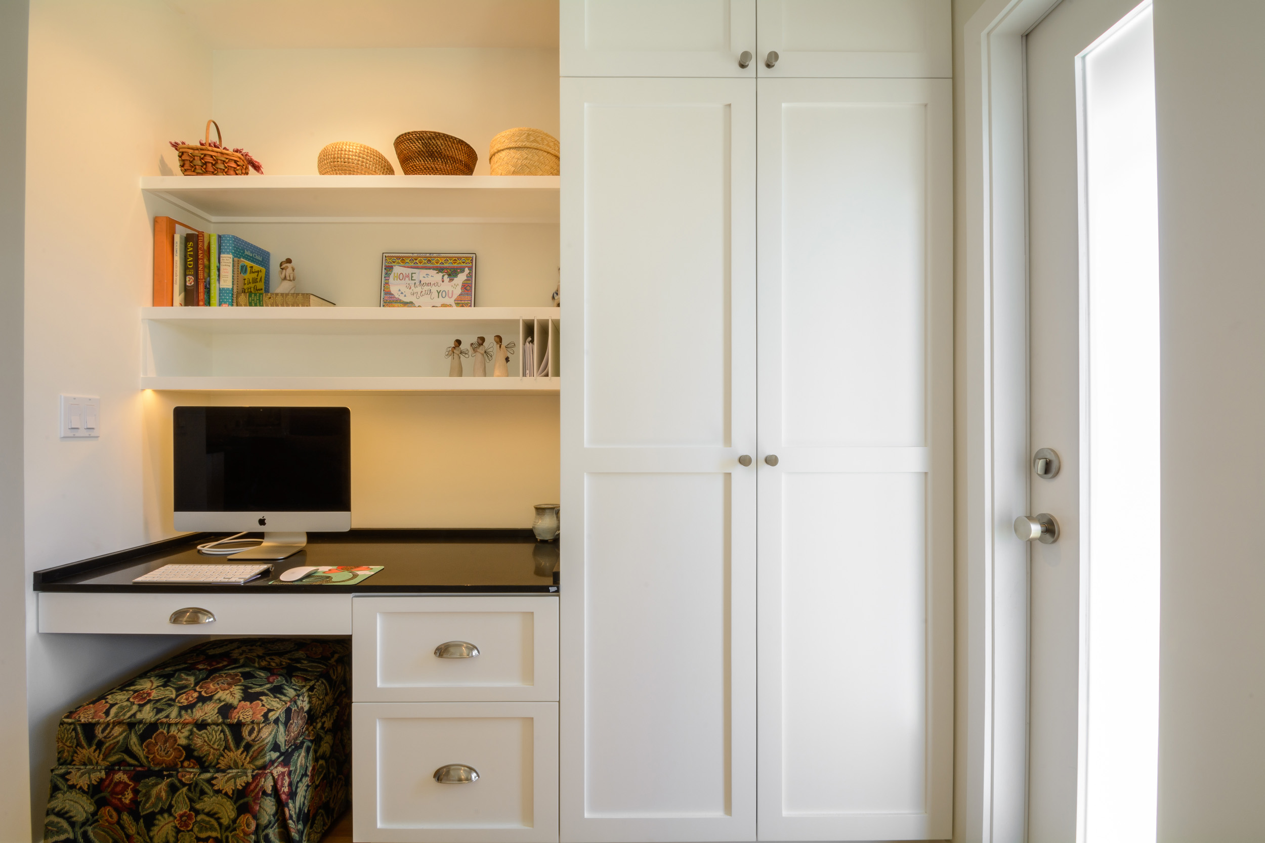 Office space for the kitchen with tall white shaker cabinets, a black quartz desk top and open shelving