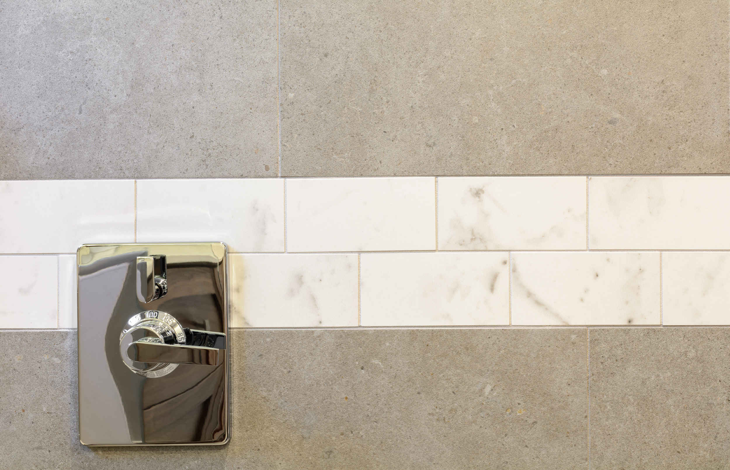 Modern shower valve with temperature indicator set in a subway border and soft grey large-format tiles