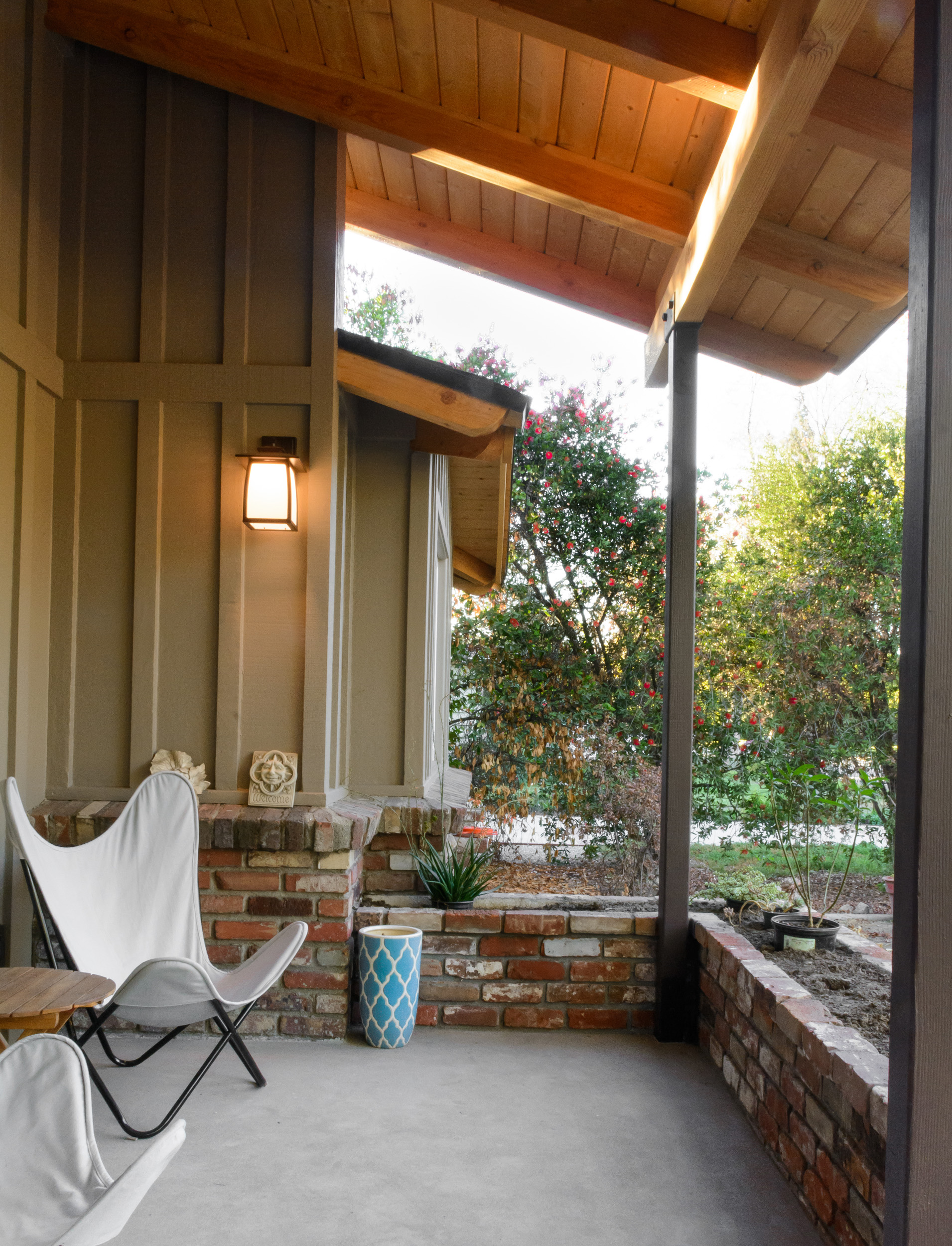 Front porch welcome and a place for respite: covered front porch with wood beams, concrete paving, a brick planter and a craftsman style wall sconce