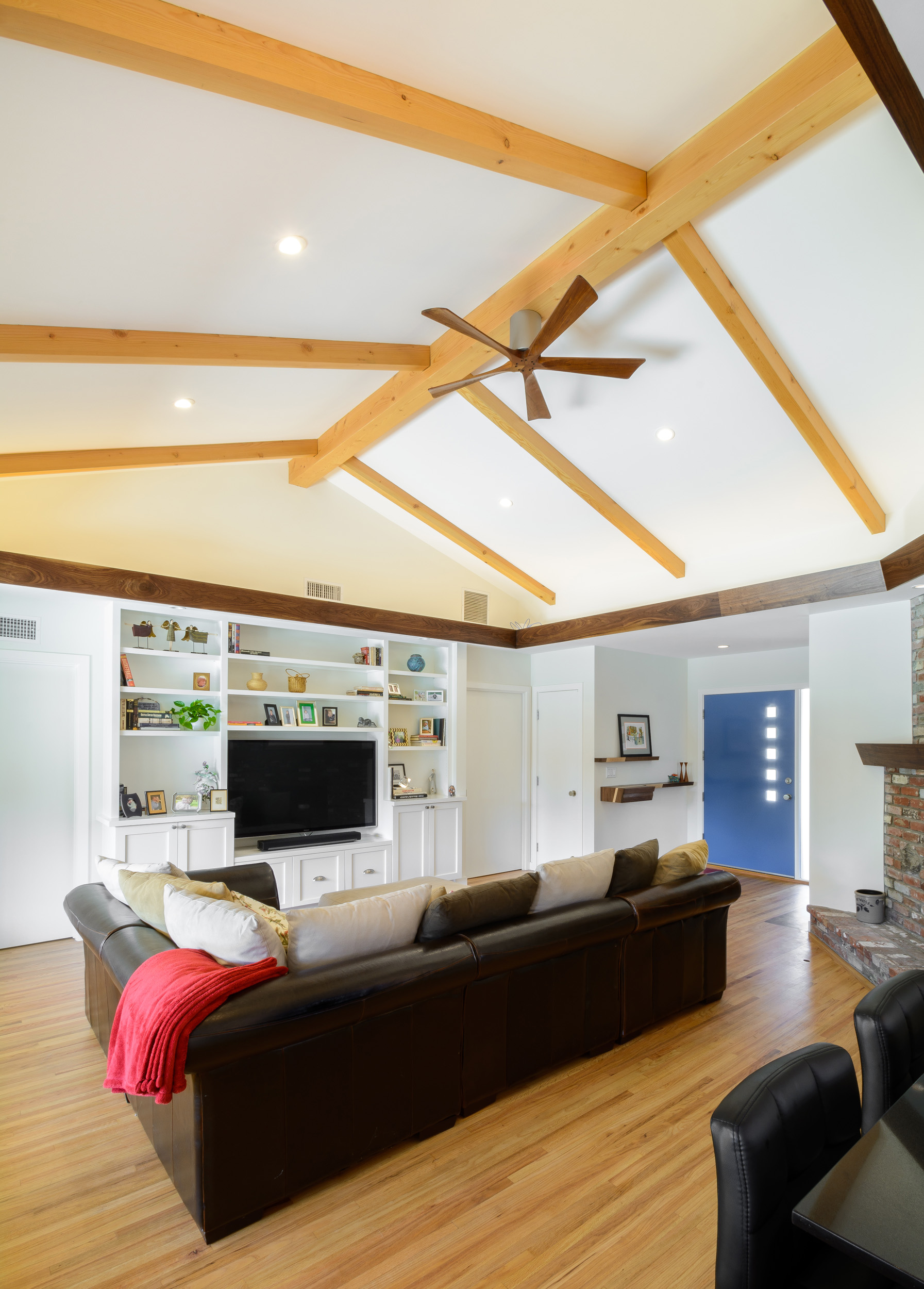Bright and comfortable living room for this mid-century ranch remodel: cathedral ceiling, exposed wood beams, recessed lighting, white walls and Shaker style cabinets for the entertainment center