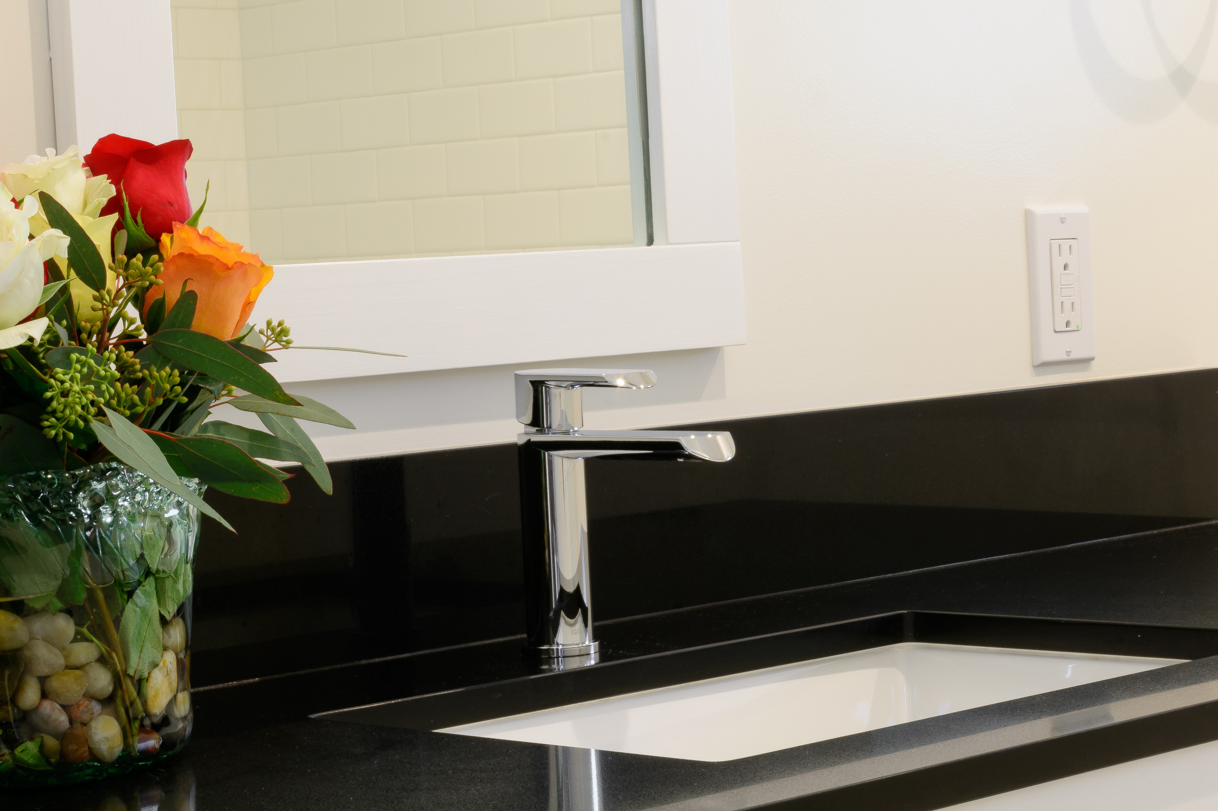 Modern sink faucet mounted on an absolute black granite vanity top and below a white framed mirror