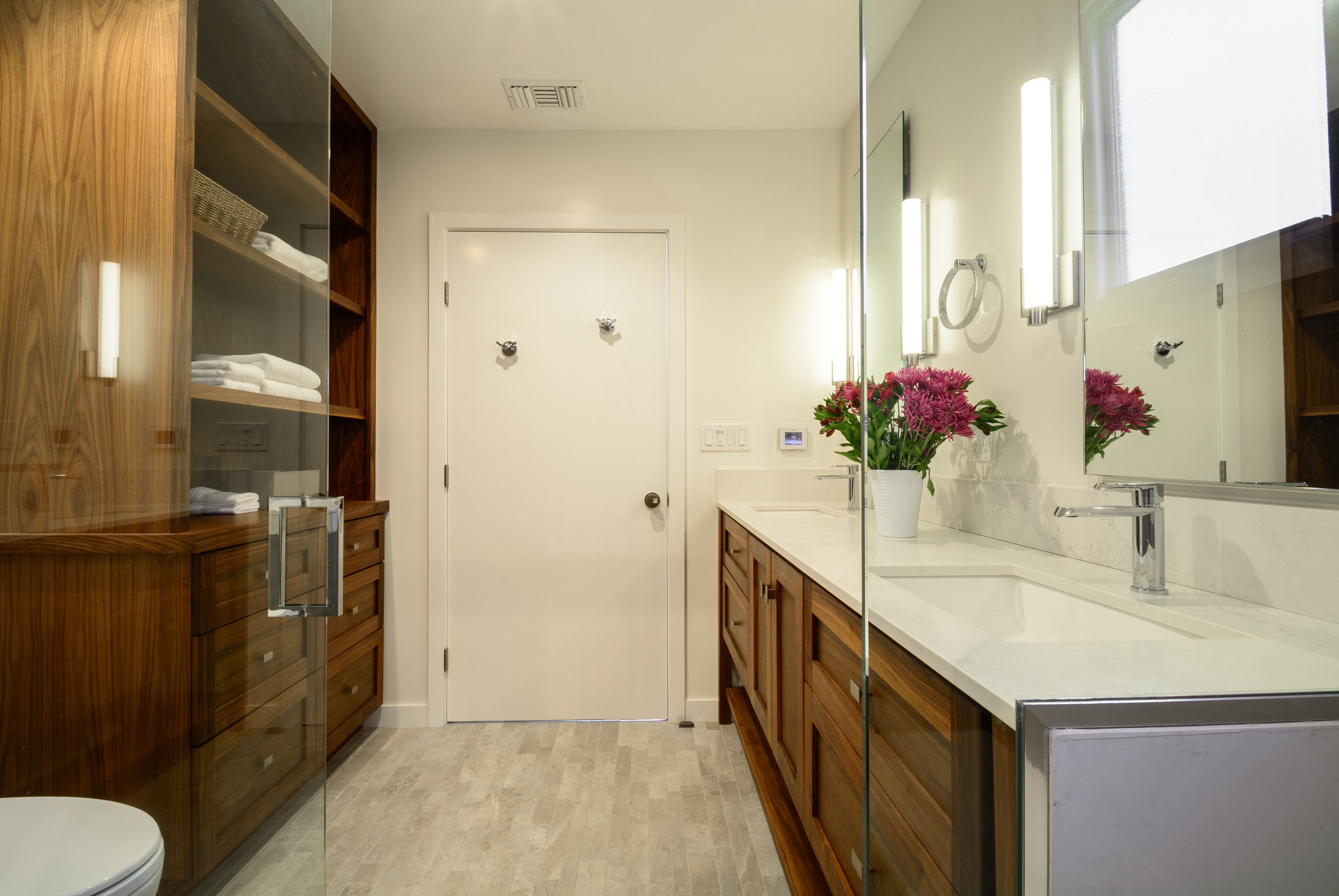 Sophisticated mid-century bathroom with an abundance of walnut storage cabinetry