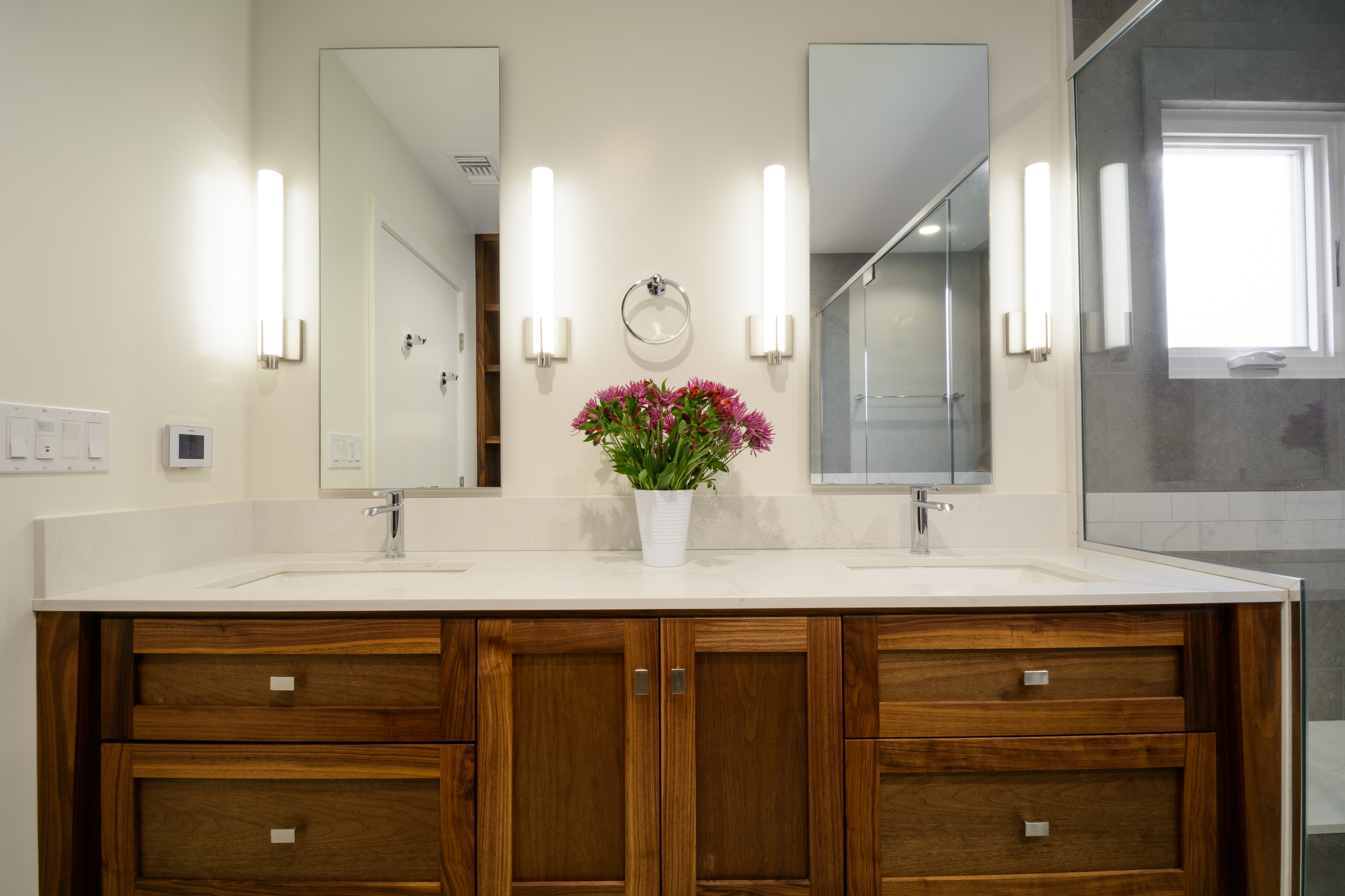 Custom walnut vanity with a white stone countertop and tall mirrored medicine cabinets