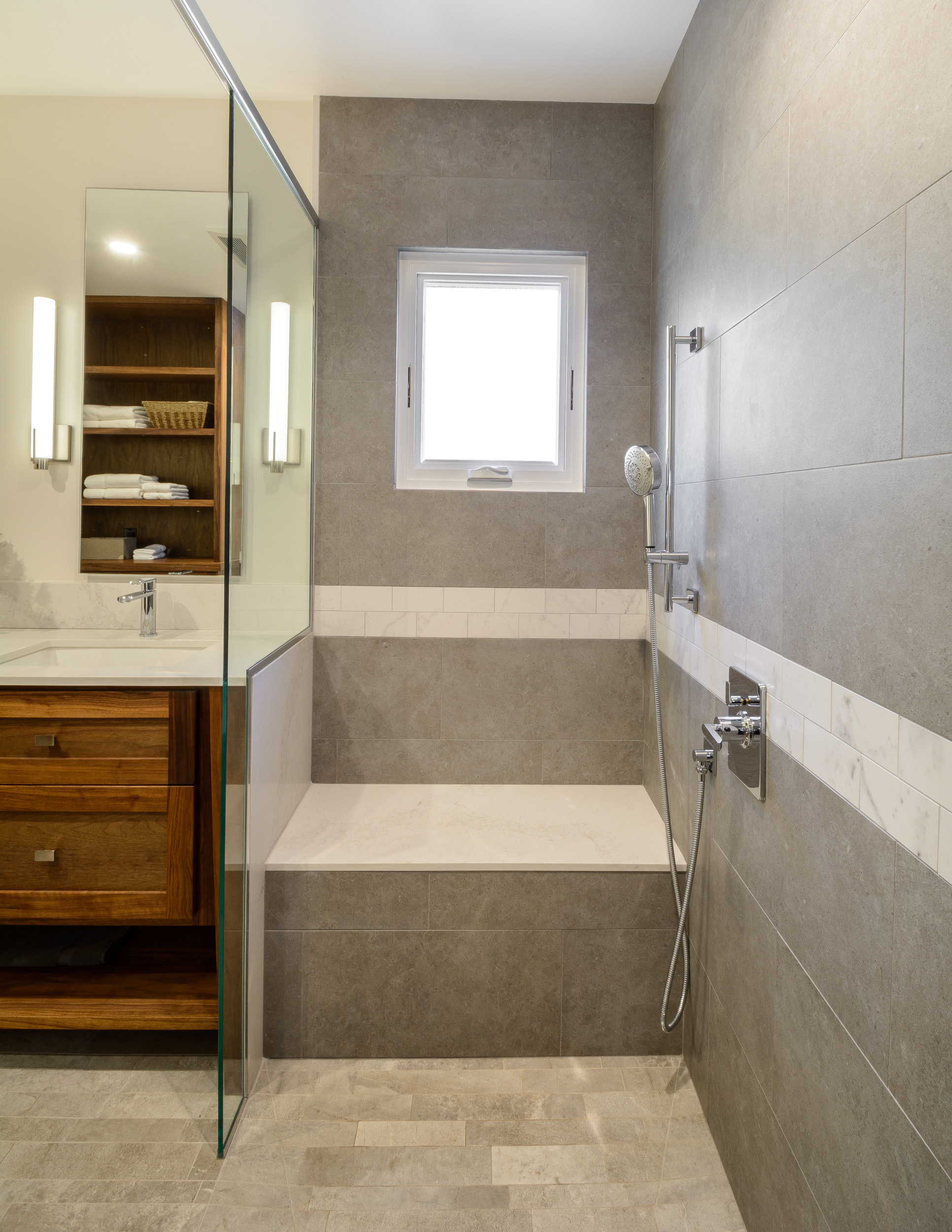 Shower seat with warming feature, small casement window for natural light, hand held shower fixture and custom walnut vanity