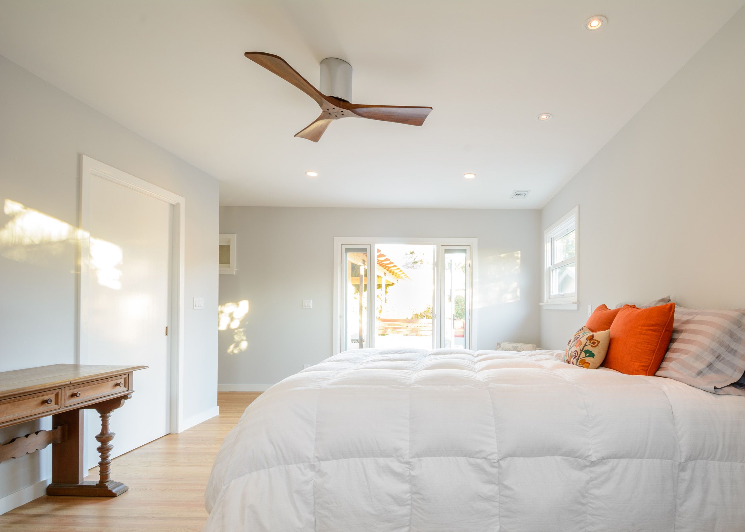 Bright and minimalist master suite addition with recessed lighting, a ceiling fan and a patio door opening onto the outside deck
