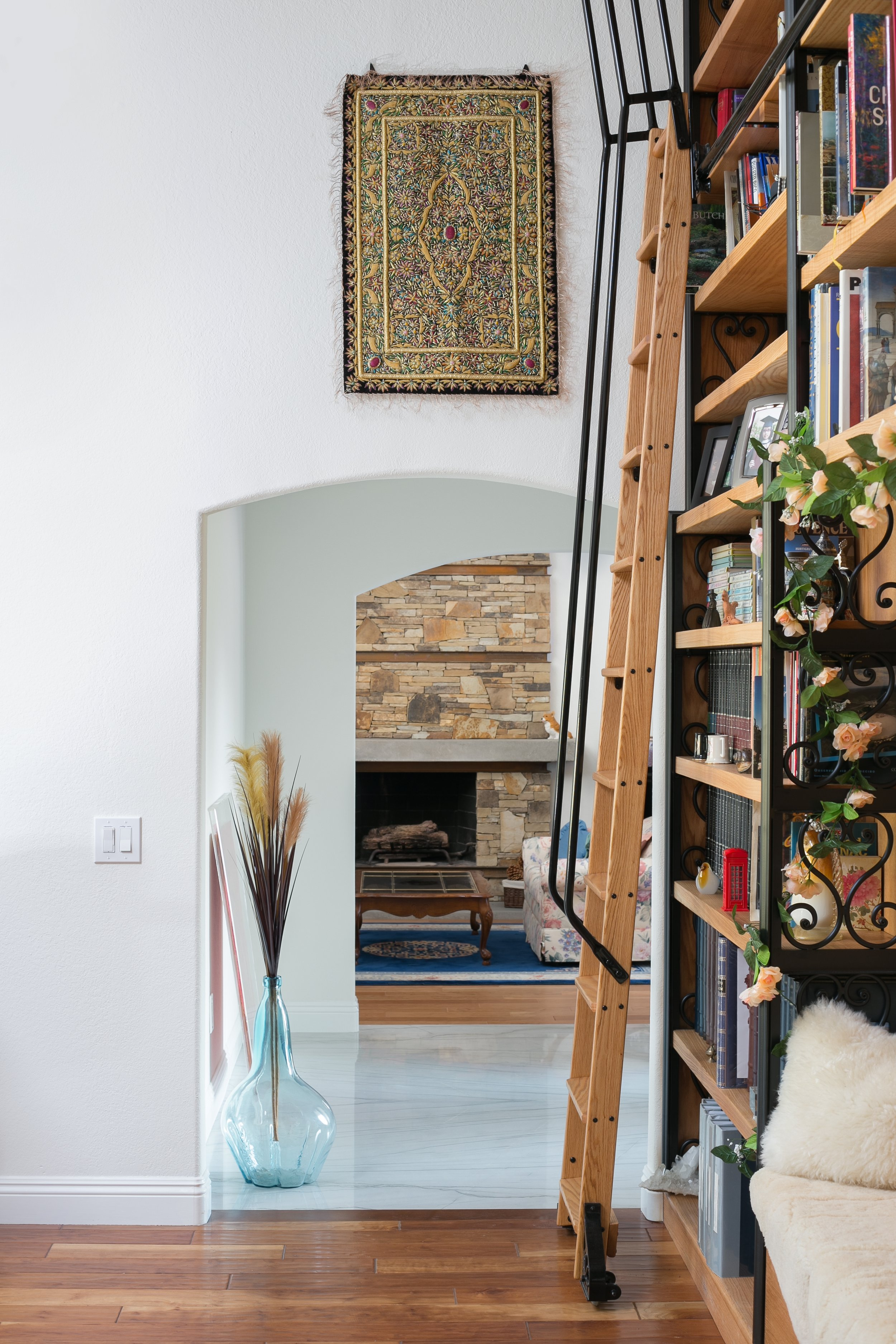 This full height custom-built library with oak bookshelves, a rolling ladder and wrought iron ornamental detail resonates perfectly with the front entry and fireplace