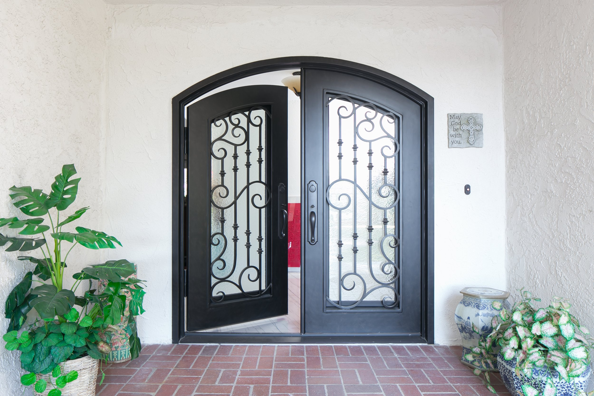 Arched steel double front door with wrought iron ornamental detail and interior glass doors for a polished entryway and front elevation