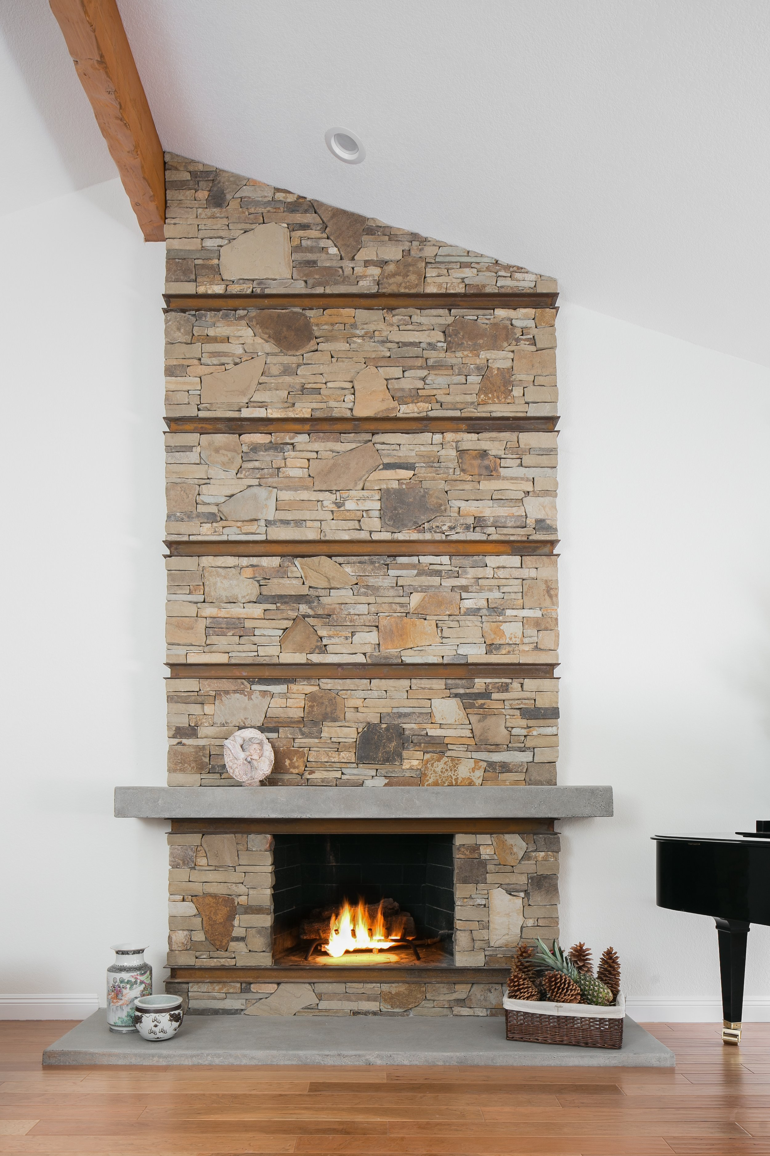Fireplace surround, tastefully made out of stacked stone with rusted channels and a polished concrete mantel and hearth, elevating the living room in all its simplicity
