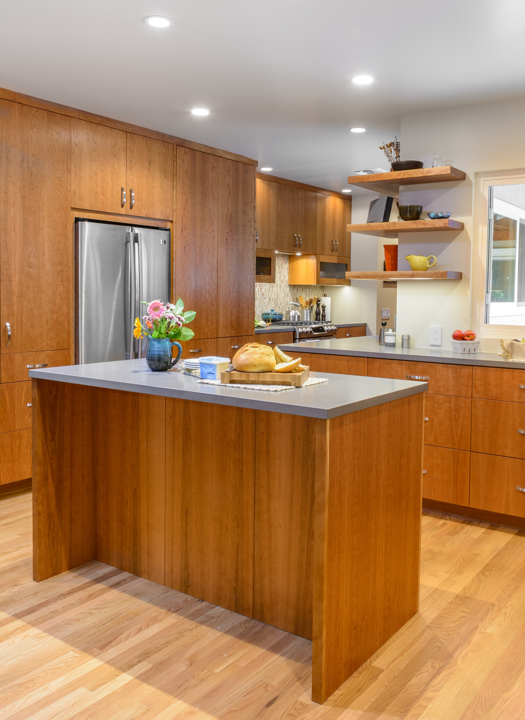 The kitchen island, custom-built cherry cabinets with quartz countertops, and floating shelves provide warmth and an easy flow to this contemporary kitchen