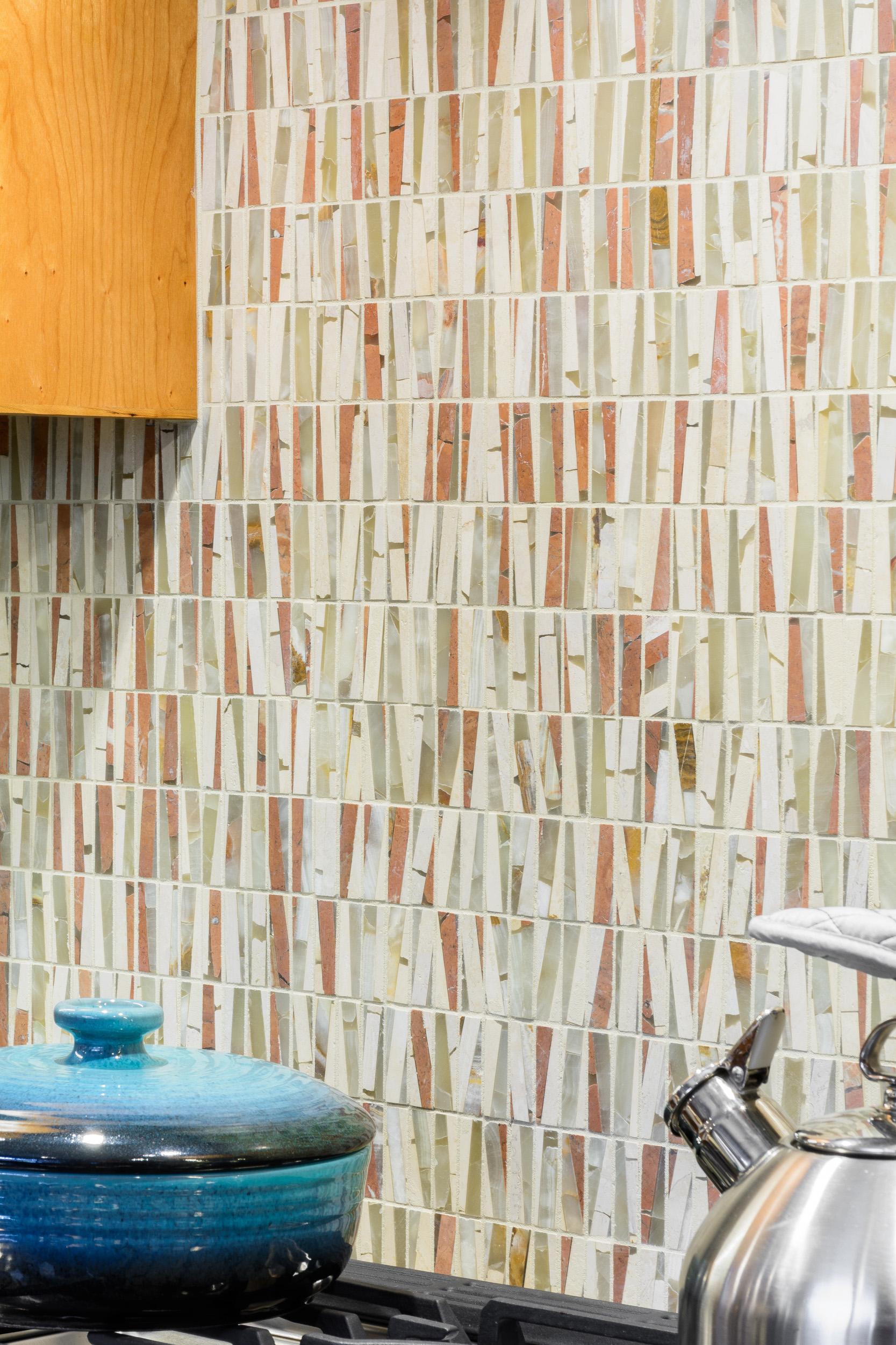 This mosaic tile backsplash over the kitchen range offers a distinctive design