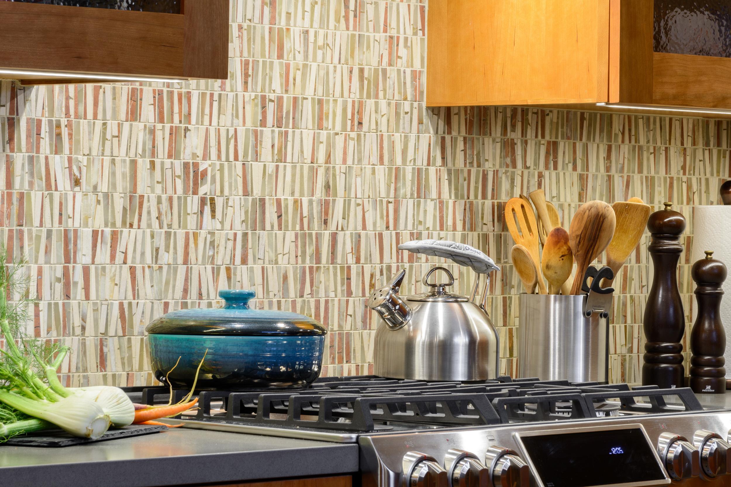 Range, grey quartz countertop and mosaic tile backsplash detail