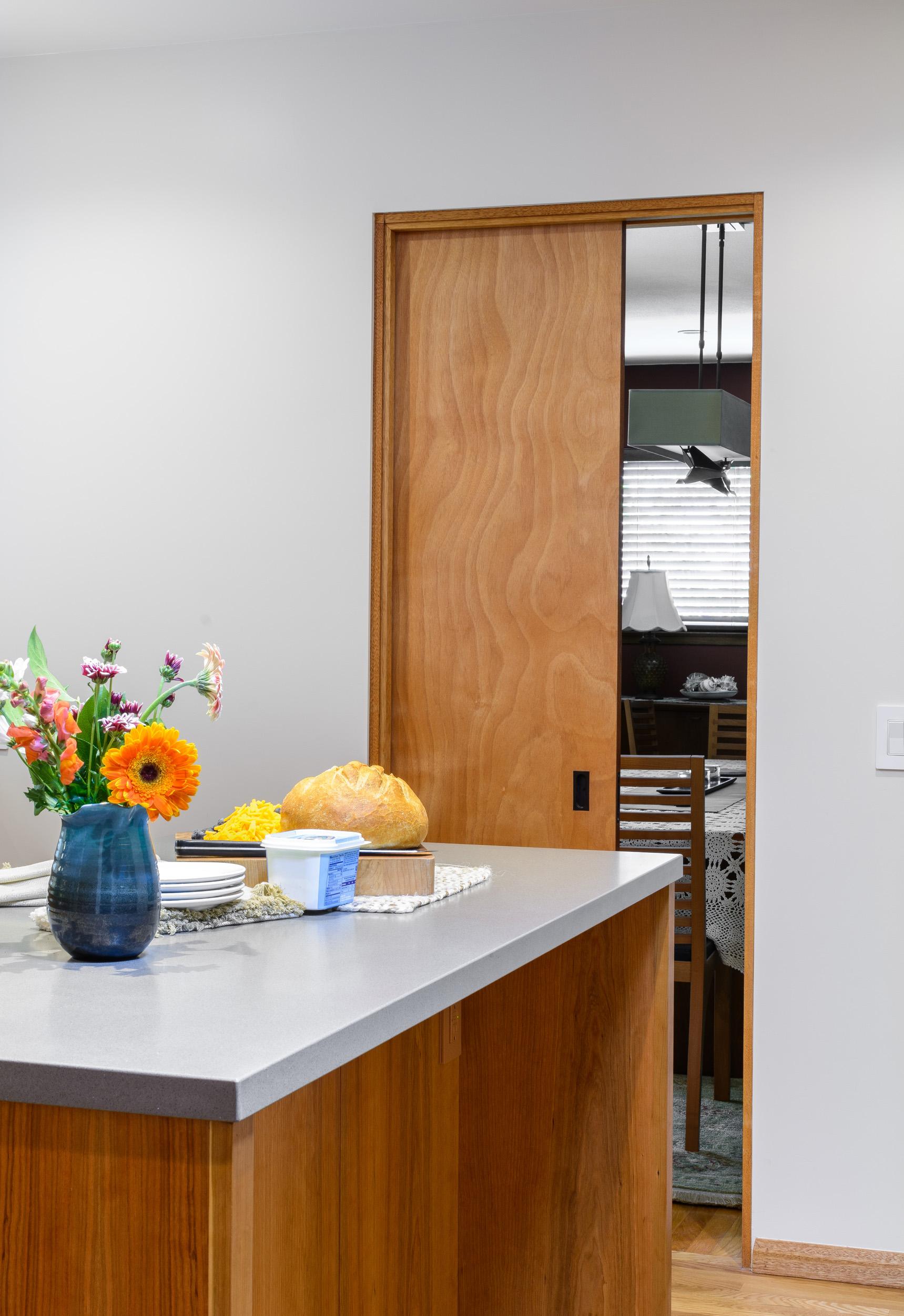 Kitchen pocket door in cherry wood between kitchen island and dining room