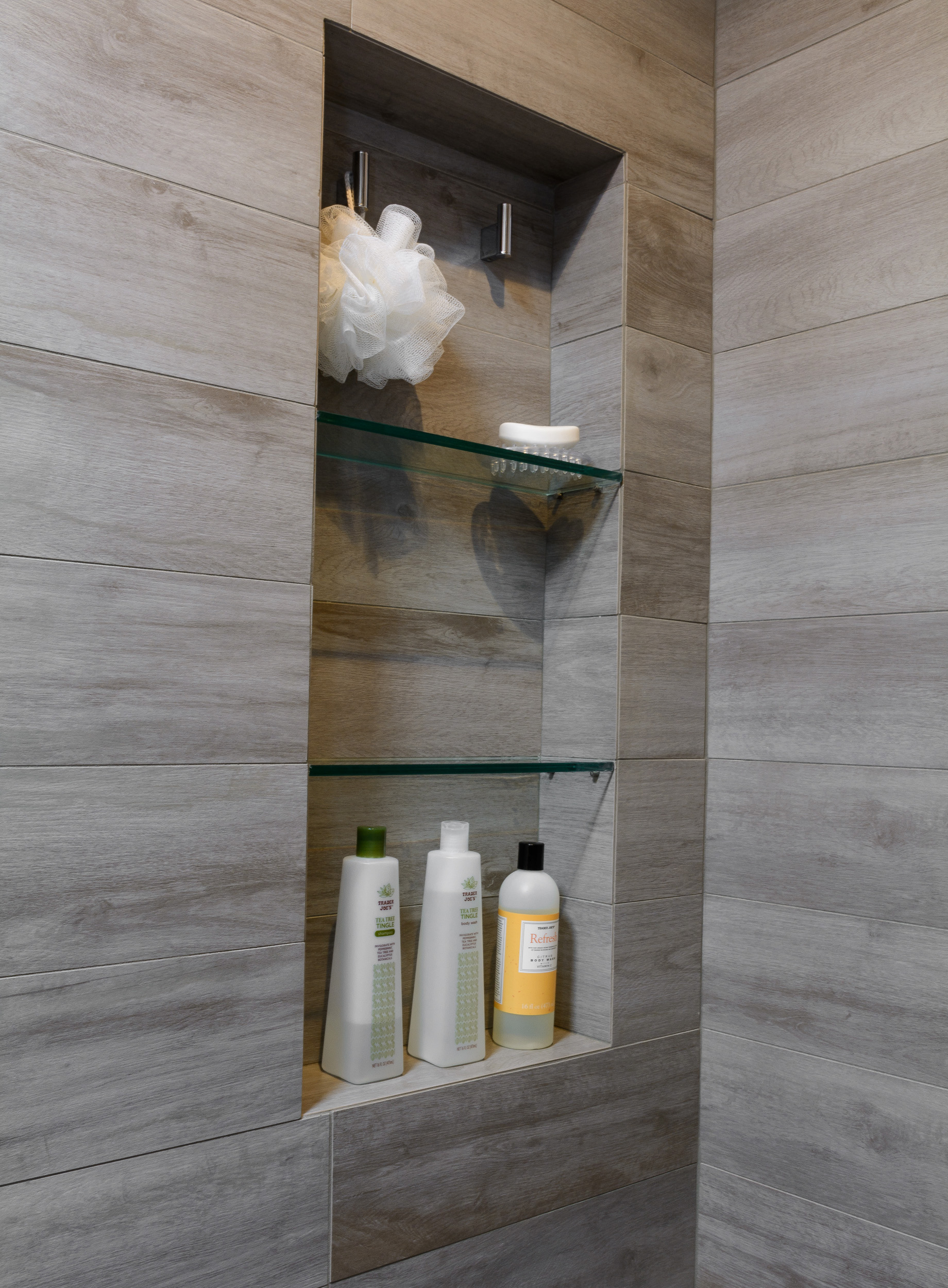Weathered wood looking shower niche with glass shelves and hooks