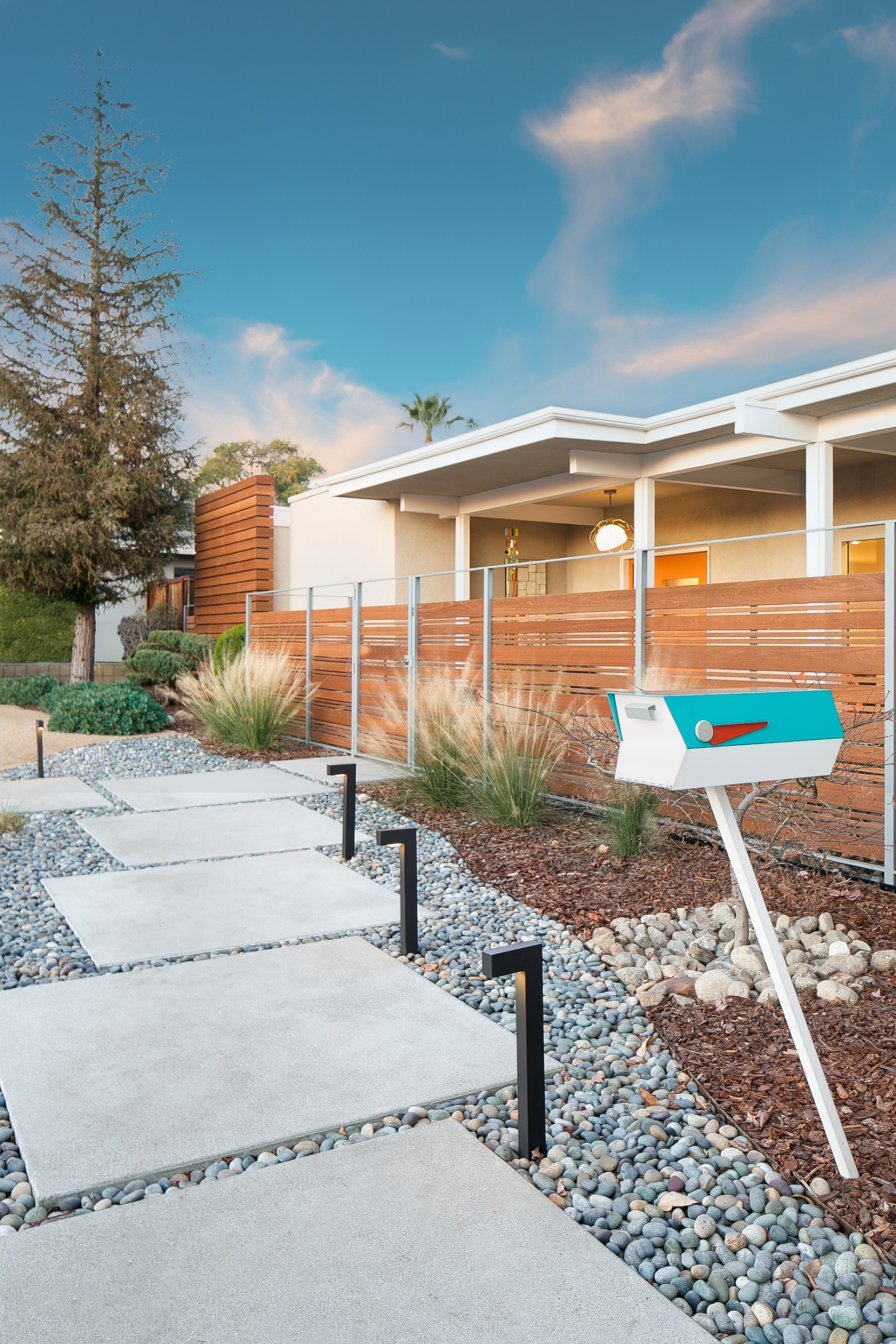 Mid-century modern exterior with a concrete paver walkway set in decorative stones, a teal mailbox, a wood fence, and the use of water-wise landscaping