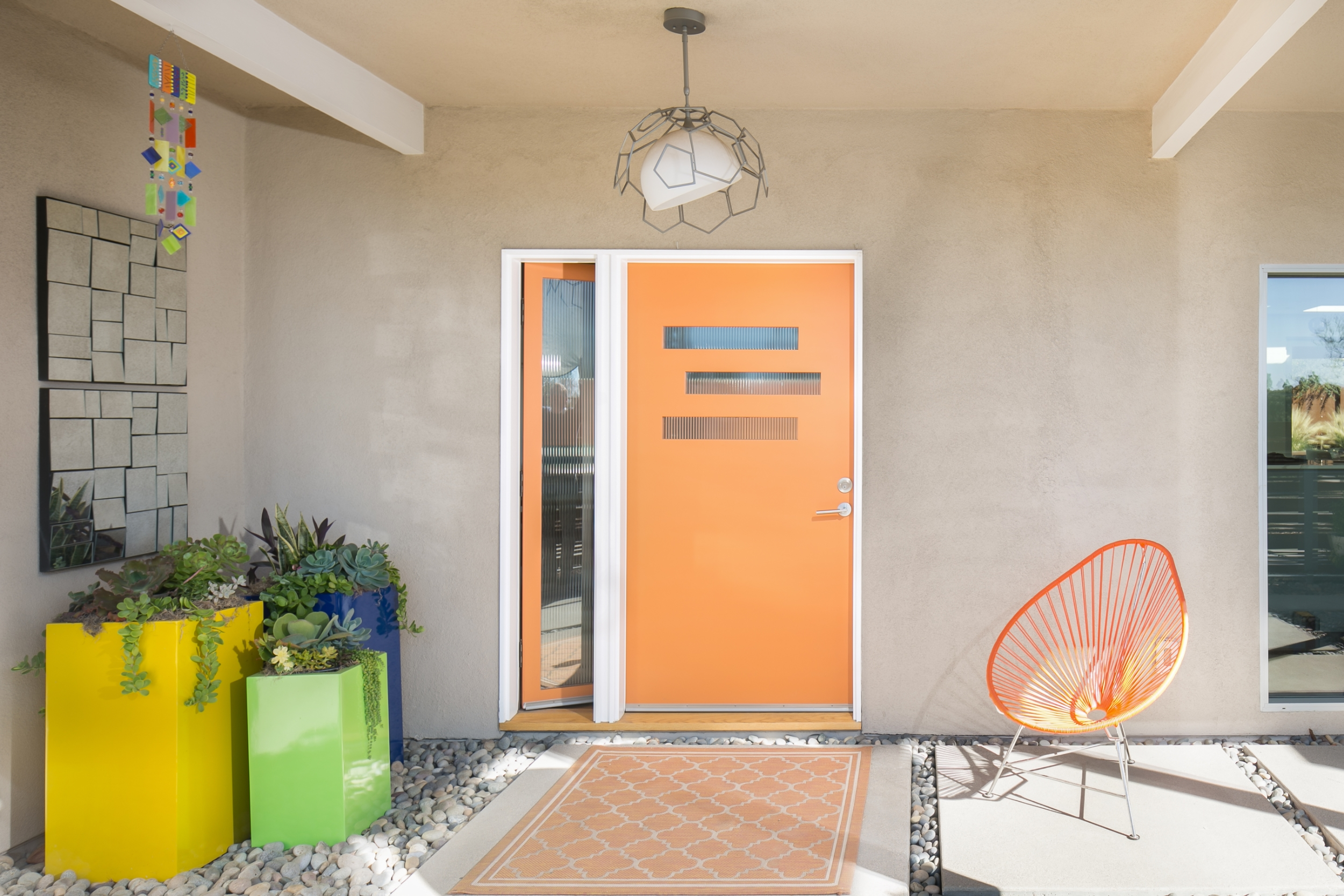 Mid-century modern entry with an orange front door and an opening glass sidelite, colorful planters, and concrete pavers set in decorative stones