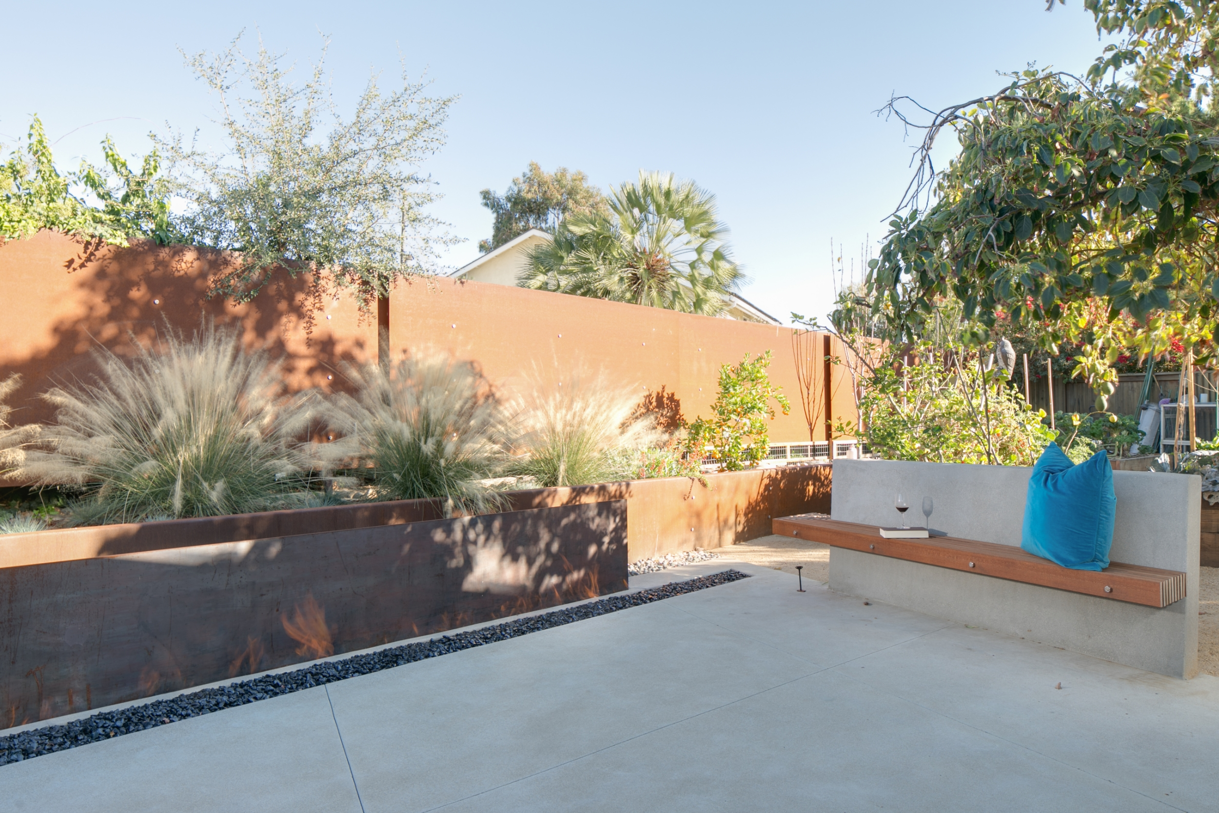 Mid-century modern backyard with an elongated built-in fire pit in front of a Corten steel wall, a concrete wall seat matching the patio slabs, and water-wise landscaping