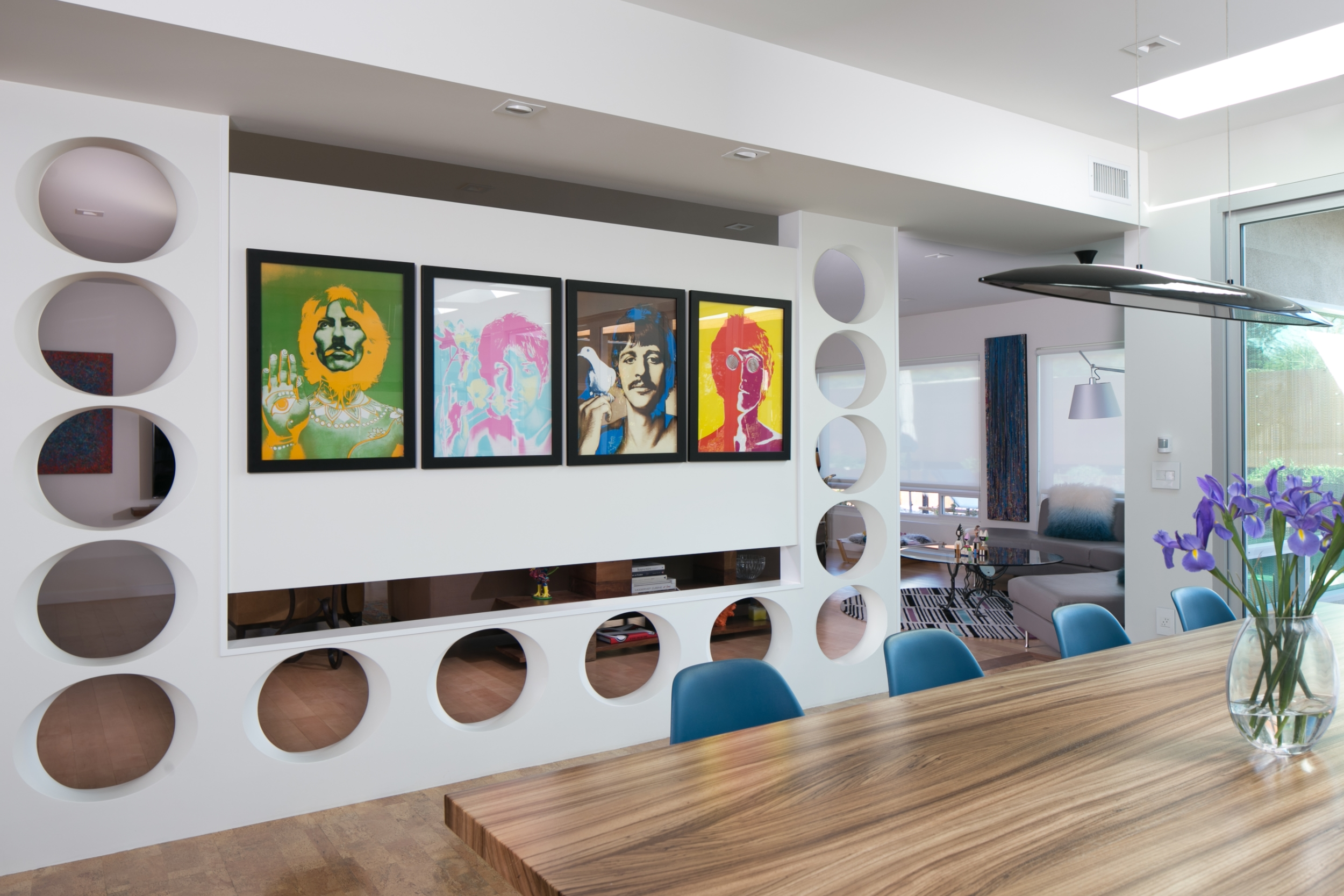 This mid-century modern dining room art wall with prints of the Beatles allows for privacy while keeping an open feel