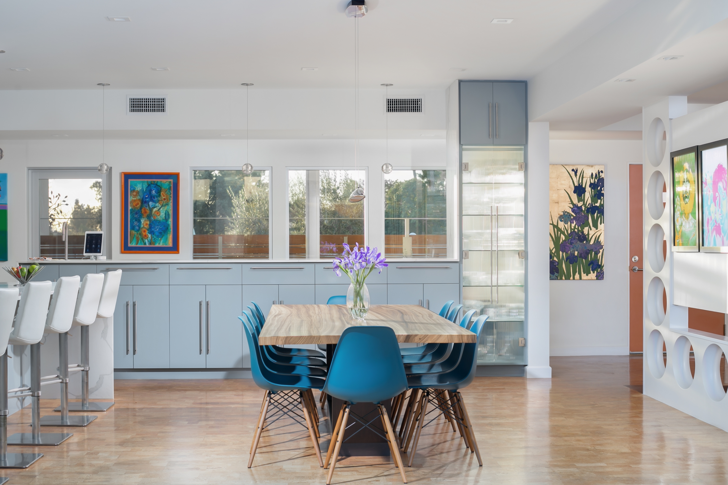 Bright mid-century dining room with an open floor plan, large picture windows, grey cabinets, quartz countertops, a cork floor and the perfect colorful art touch