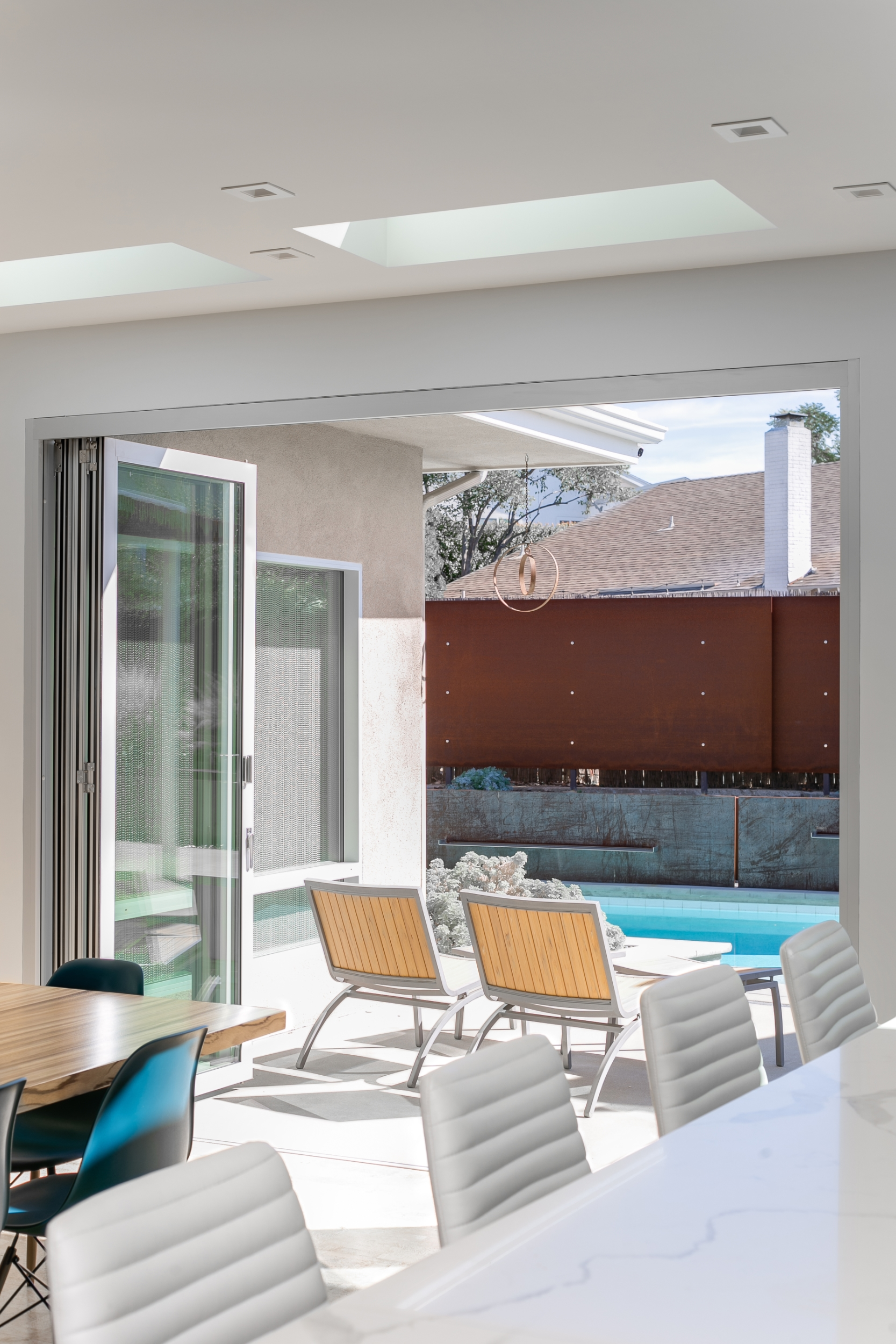 Indoor-outdoor living: the folding glass doors open the kitchen and dining room onto the patio and the pool, accentuated with a wall of Corten steel