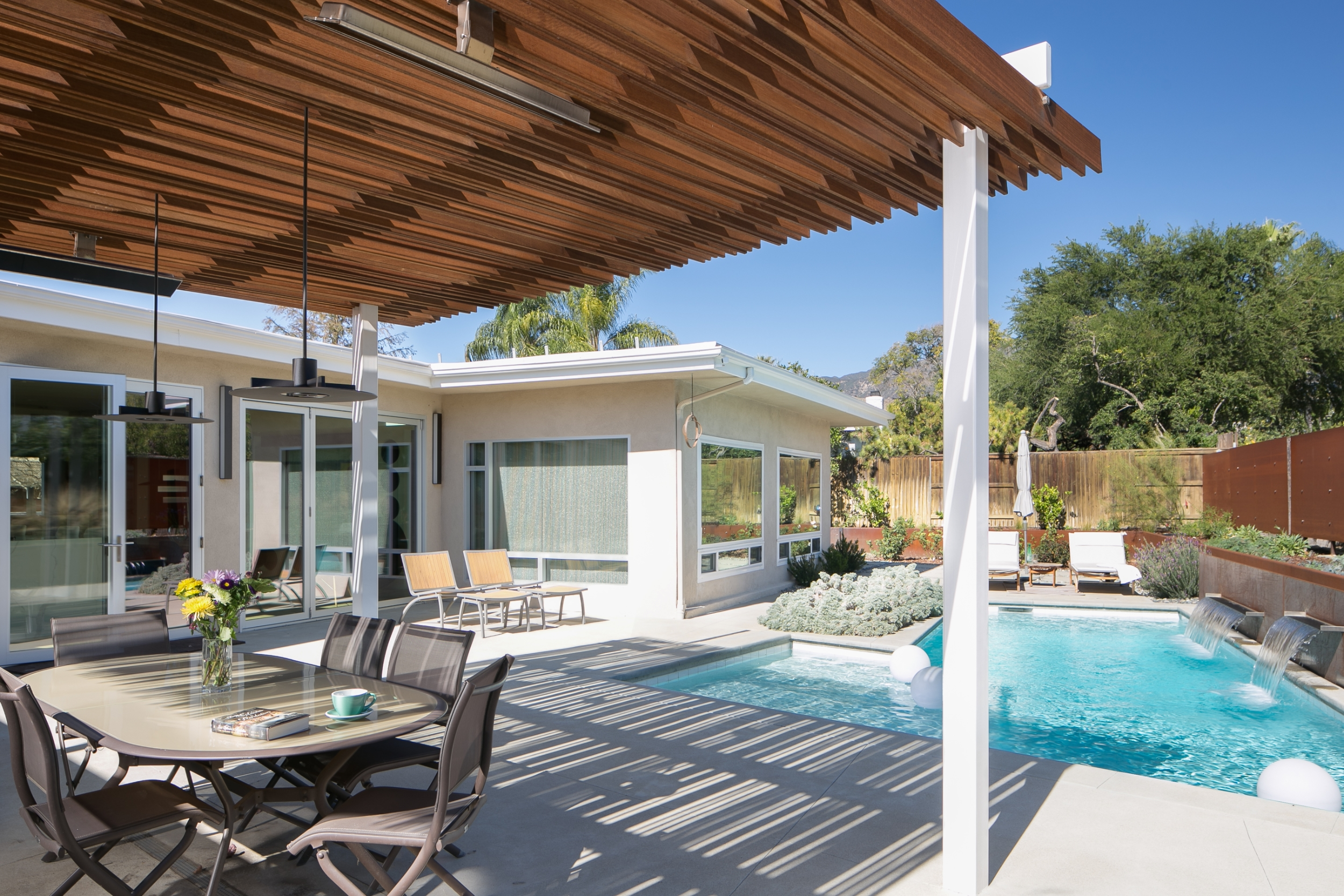 Mid-century modern backyard with water-wise landscaping, a pool accentuated with waterfall spillways off of a Corten steel wall, and a pergola for outdoor dining