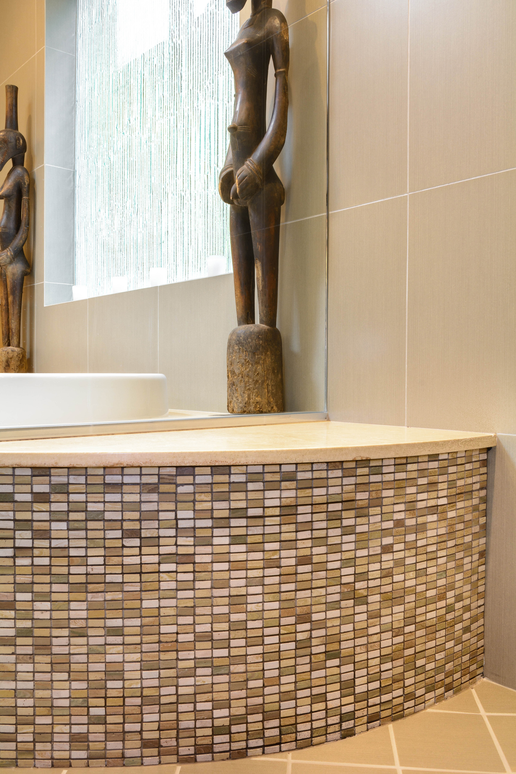 Mosaic tile bathtub surround combined with large-format wall tiles, diagonal field floor tiles and art pieces