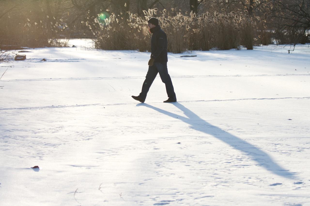 A man walks across the frozen lake