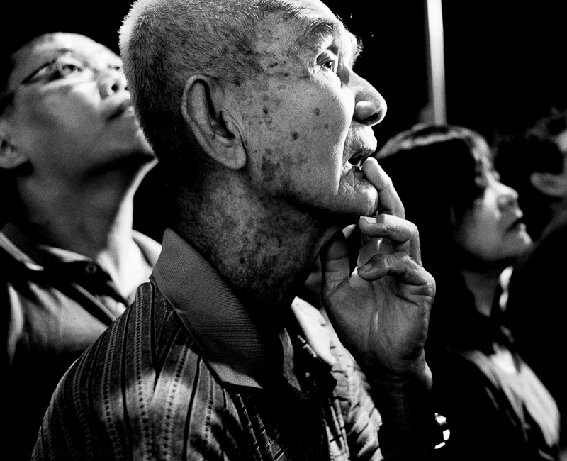 Old man looking up at preparations for an acrobatic lion dance at Chinese New Year, Penang, February 2013