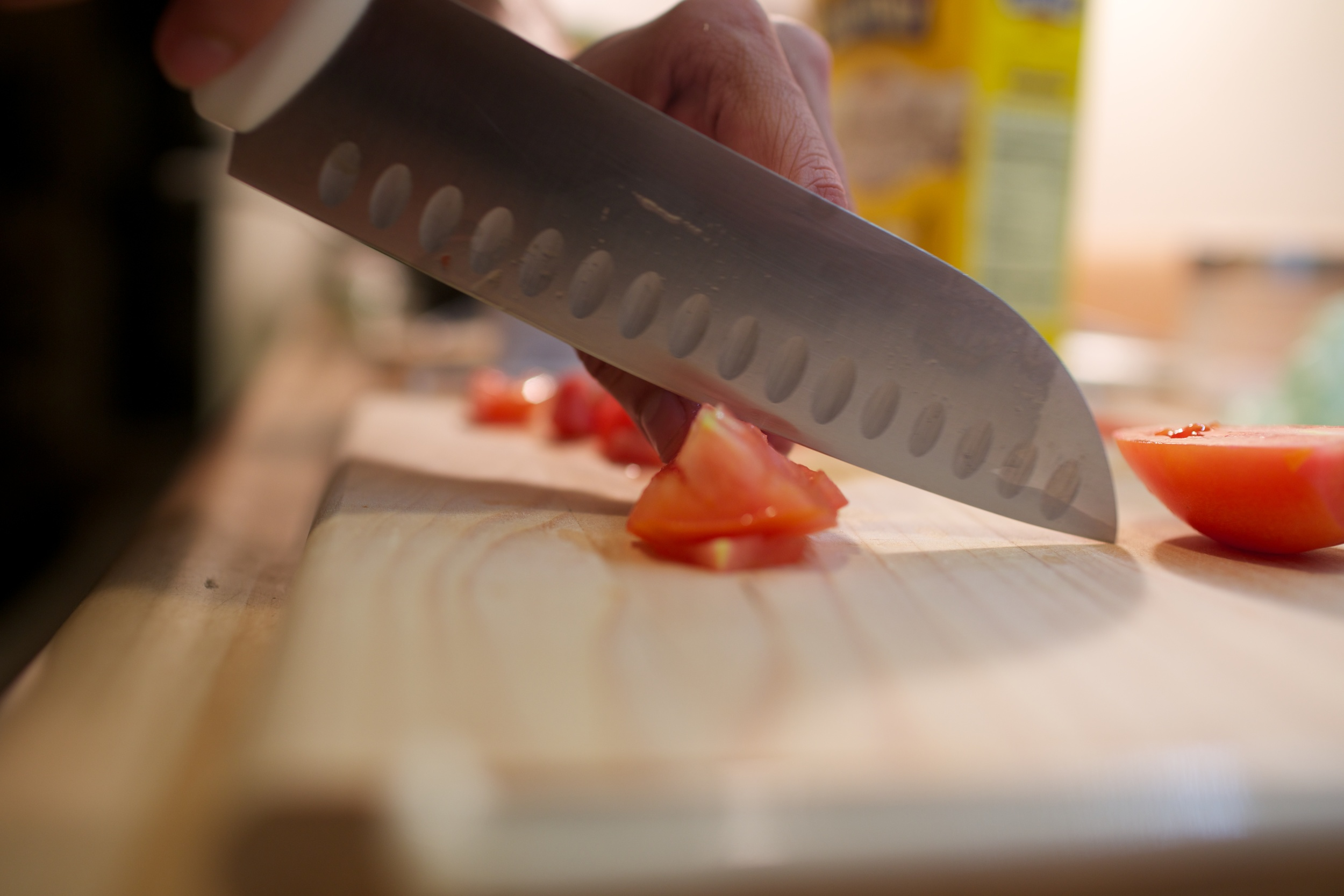 Kunal slicing tomatos, and hopefully not a finger.