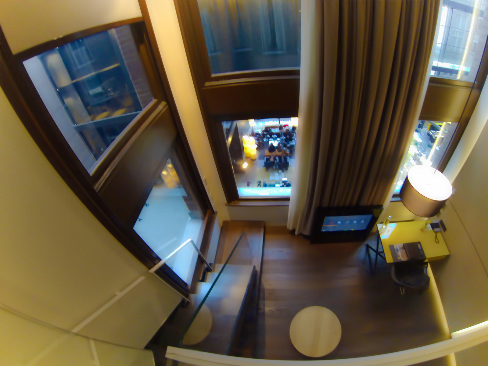 conservatorium-hotel-amsterdam-bedroom-view-of-desk-tv-motorized-drapes-and-shades-overlooking-lobby.jpg