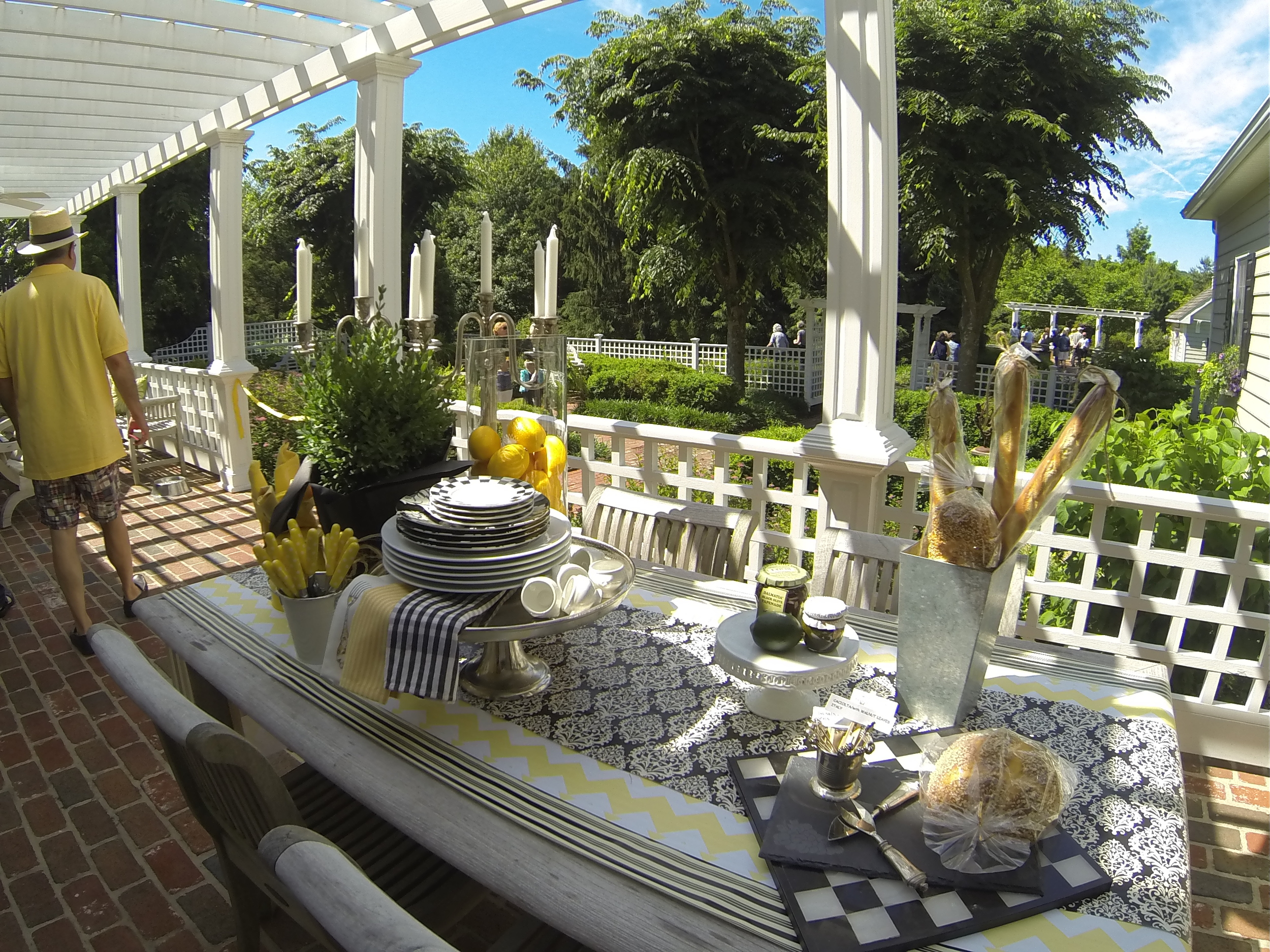 Styled back porch highlights a summer brunch gathering underneath the pergola.