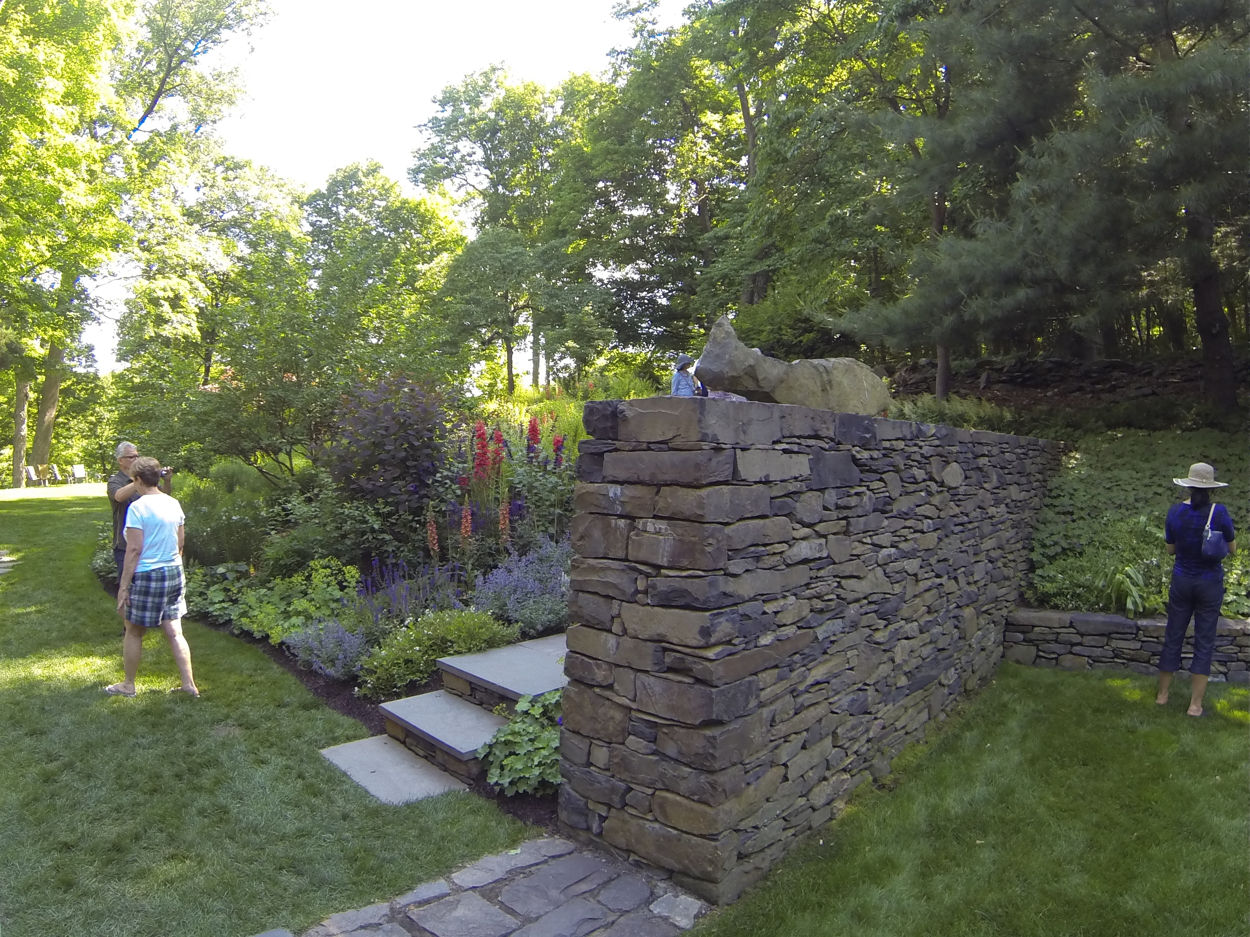 The sunny hillside leads to terraced lawn panels with trees, shrubs, perennials, and annuals.