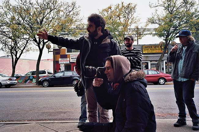 Director David Mitchell looking through viewfinder while DP Michael Gioulakis points the way. To the right is Marc-Antoine the gaffer and far right is Anthony Schrader key grip.