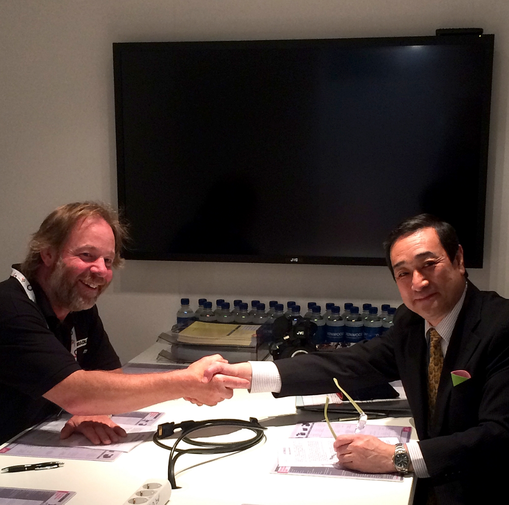 David Bradley and JVCKENWOOD's Hisao Kikuchi VP and Executive Officer shake hands on the sales agreement between the two companies.