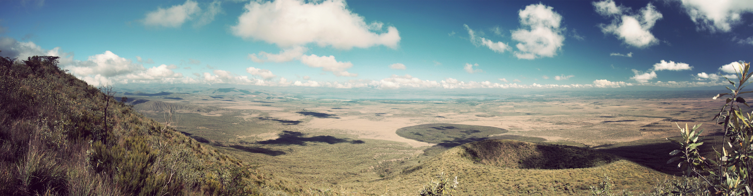 Panorama over the valley towards Lake Naivasha: the smaller crater was a vent that exploded before the big explosion (details are hazy on this), the dark circular area is the lava flow.