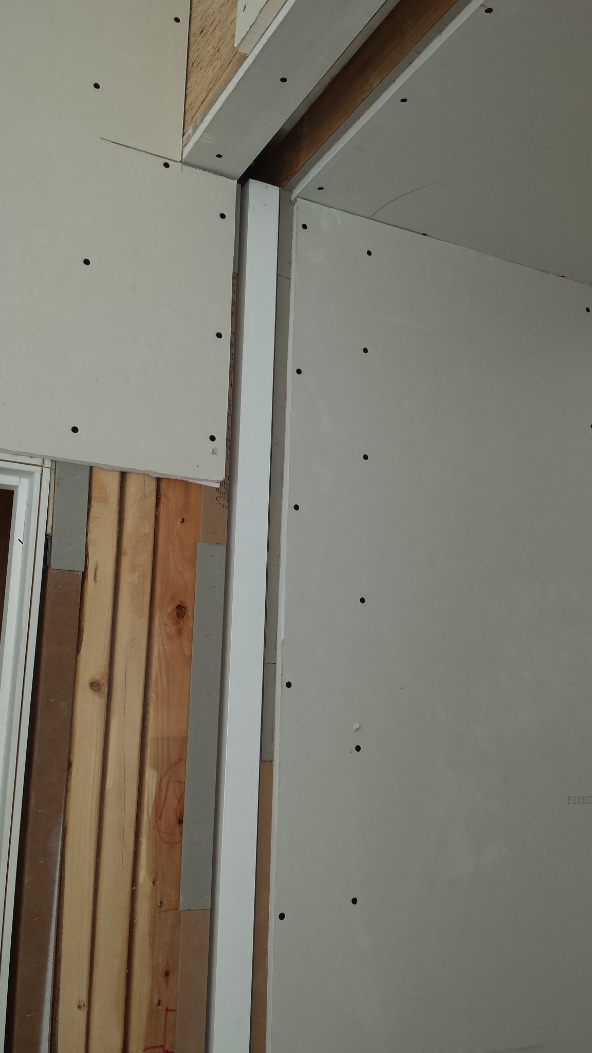 The areas around the opening are shimmed with strips of cardboard to get the drywall flush with the edge of the door.