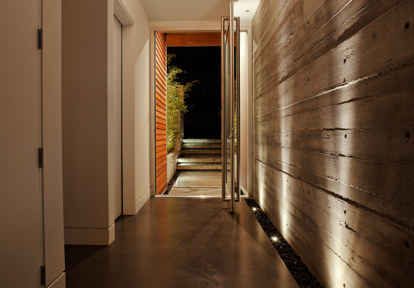 A beautiful example of a feature wall. The board formed concrete makes a bold statement. The material is very textural, spiking curiosity and asking to be touched. The wall is pulled away from the floor and separated by stones. While the floor is also concrete, the wall is distinctly different. The up lighting highlights the wall and further emphasizes its significance.
