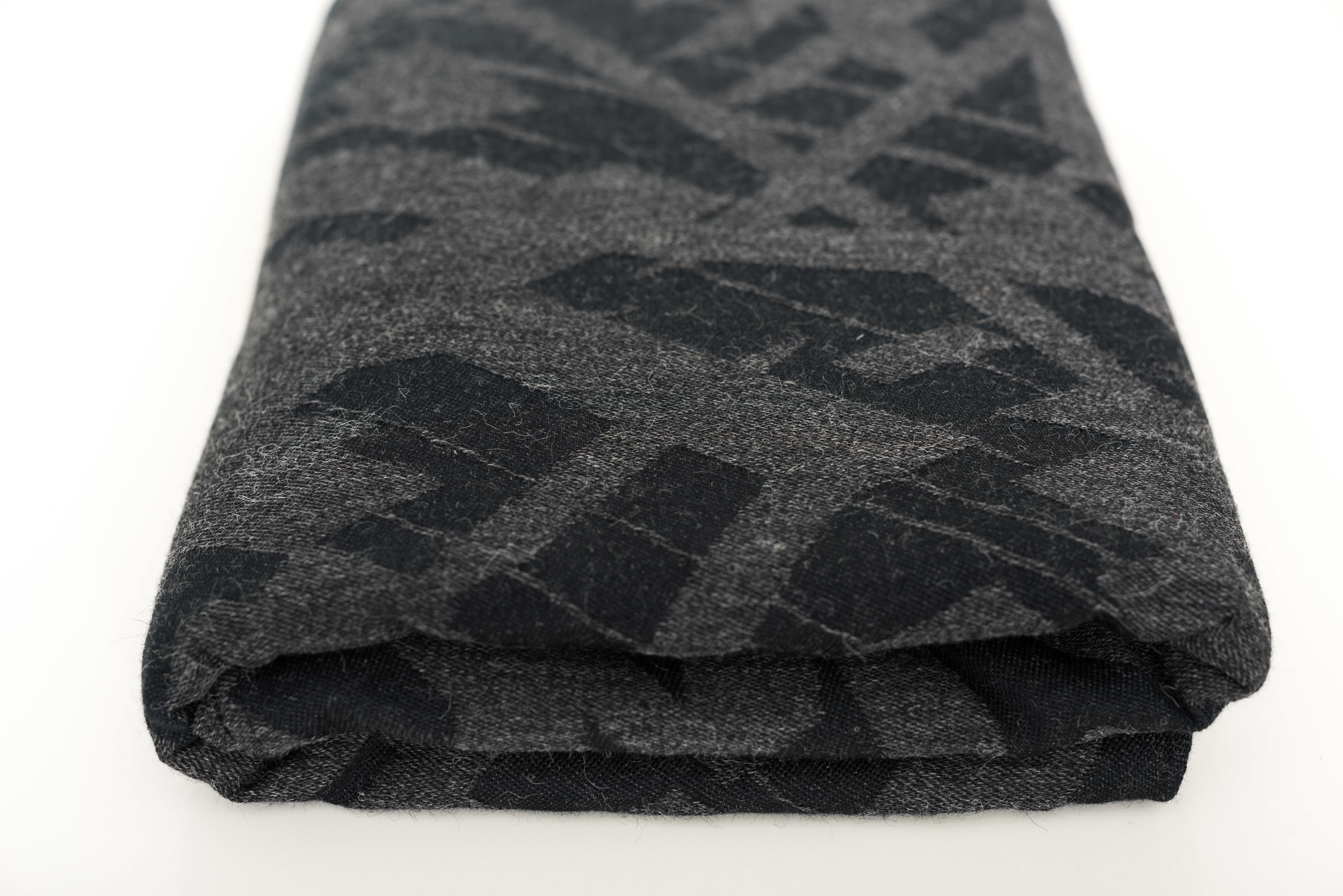 Futurism Charcoal · 66% cotton 34% alpaca  Handwash, lay flat to dry  Futurism Charcoal Alpaca is shockingly thin for a wool wrap.The right amount of thickness combined with the temperature regulating properties of wool make it suitable for most climates. This cotton and alpaca mix create a wrap that breaks in wonderfully soft and drapey. The added magic of a black warp takes this wrap to the next level.