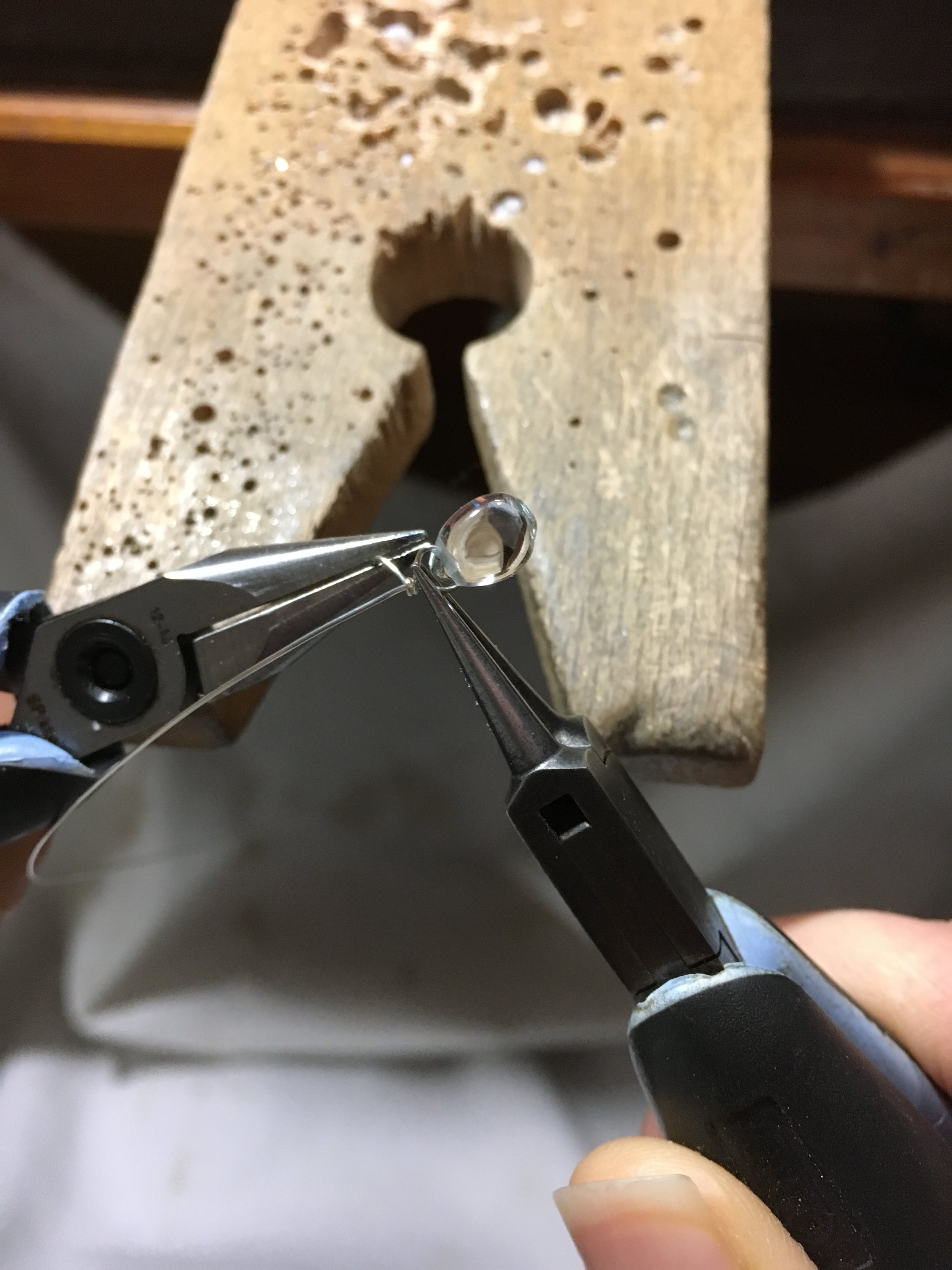 Wire wrapping an aquamarine teardrop