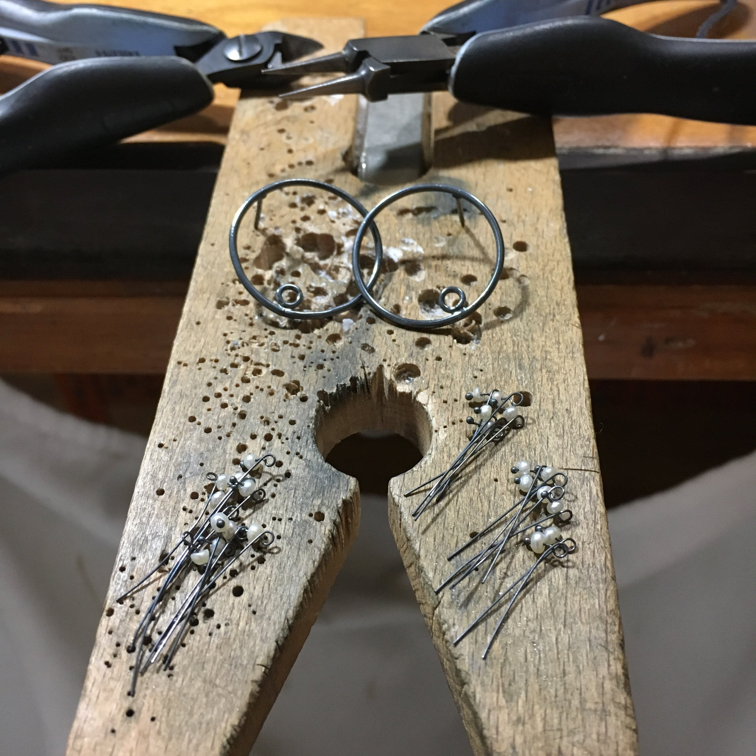 A pair of Adva hoop earrings in pearls and oxidized recycled sterling silver sits on Michelle Pajak-Reynolds workbench. Photo credit: Michelle Pajak-Reynolds