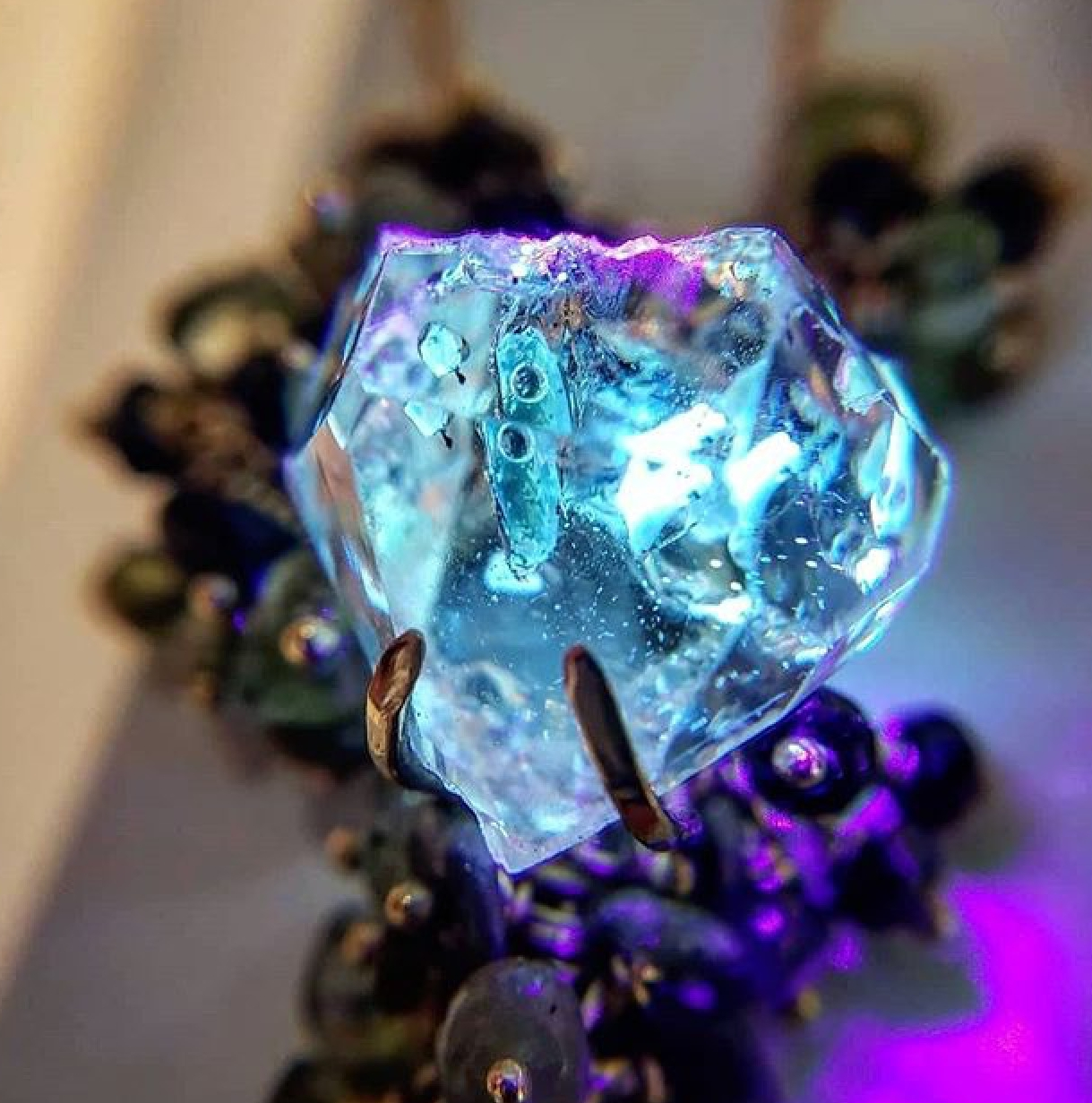 Detail of the golden enhydro quartz in Michelle Pajak-Reynolds's Desma pendant fluorescing under UV light. Photo courtesy: Benjamin Guttery/Third Coast Gems