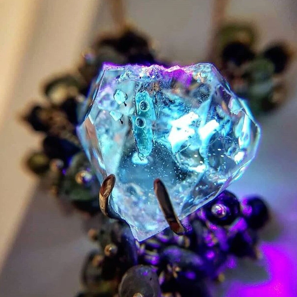 Detail of the golden enhydro quartz crystal in Michelle Pajak-Reynolds's Voyageuse Collection Desma pendant fluorescing under UV light. Photo courtesy: Benjamin Guttery/Third Coast Gems